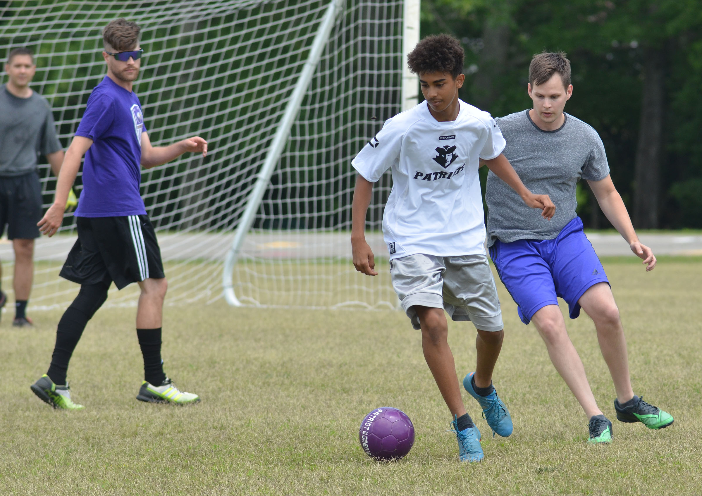 CHS sophomore David Silva kicks the ball, with alumni player Jeff Muncie on his heels.