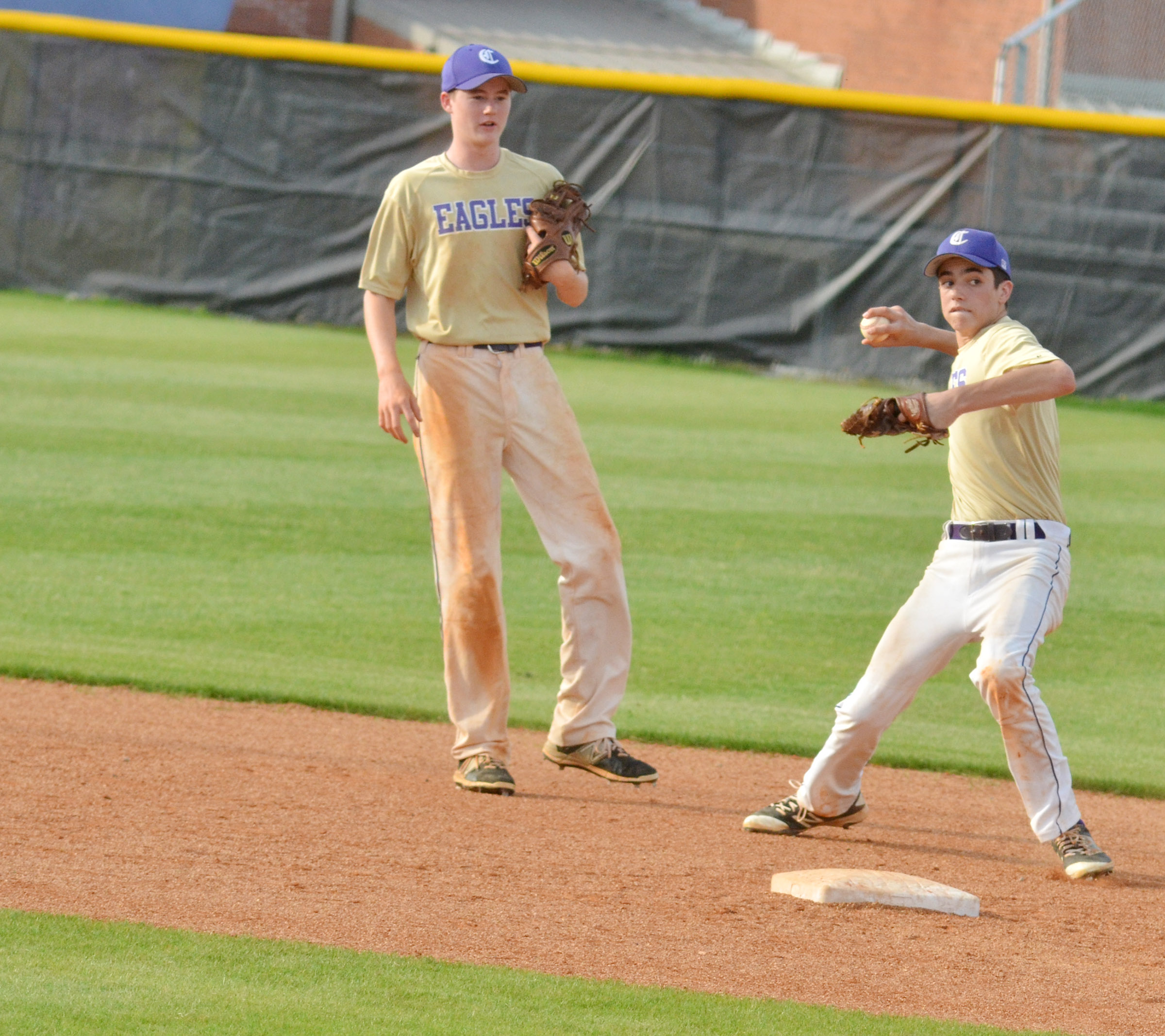 CMS eighth-grader Kameron Smith throws to first for an out as classmate Tristin Faulkner looks on.