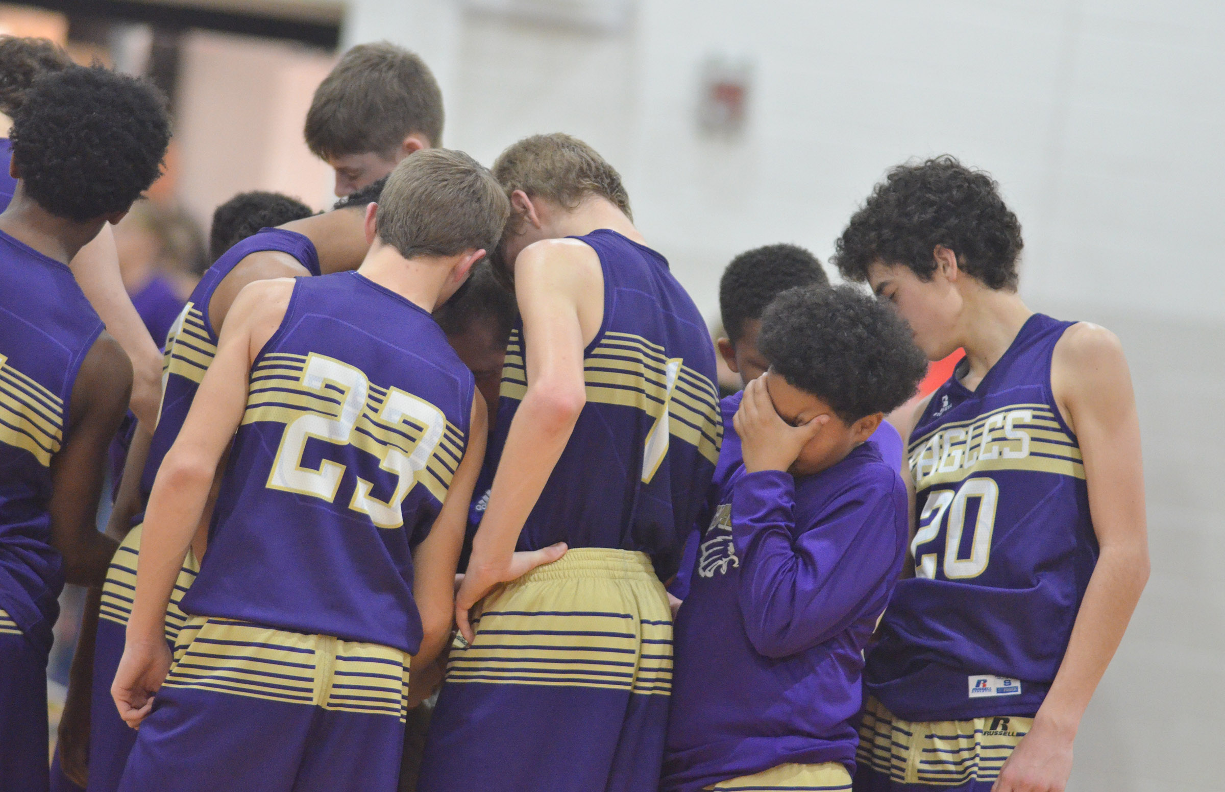 CMS boys' basketball players pray after their game.