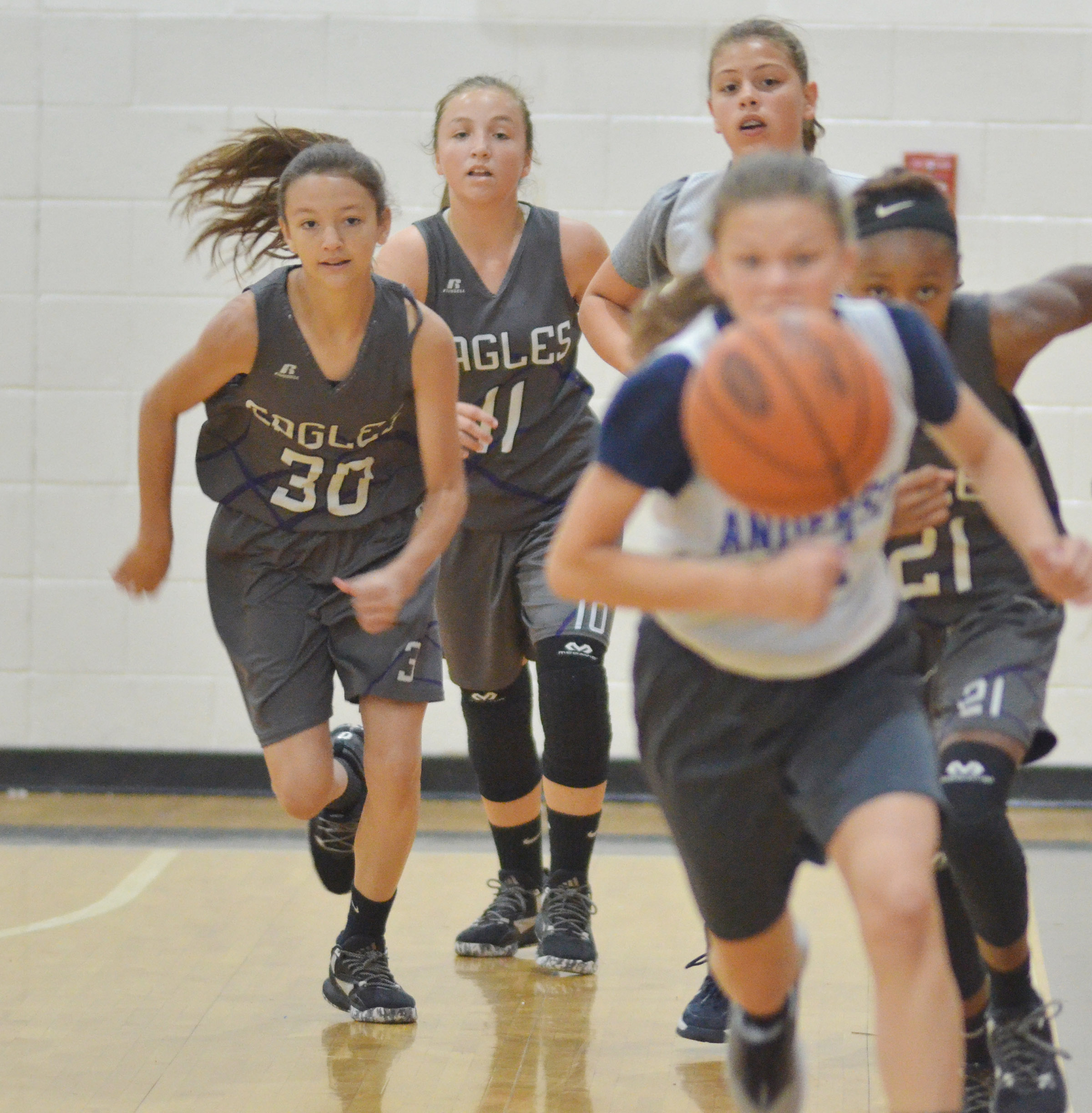 From left, CMS seventh-grader Bri Hayes and eighth-graders Lainey Watson and Bri Gowdy run for the ball.
