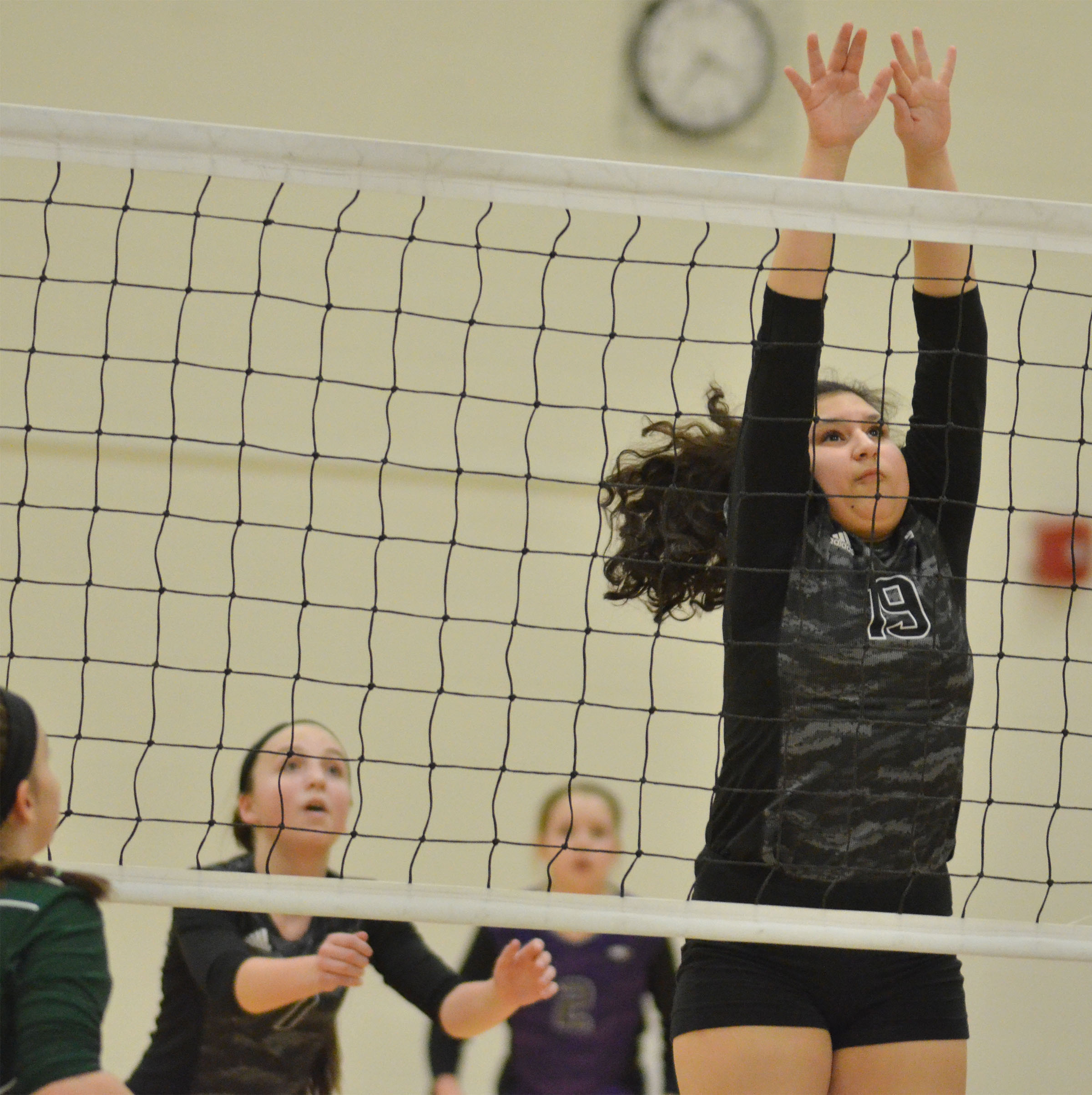 CMS eighth-grader Anna Clara Moura jumps to block the ball.