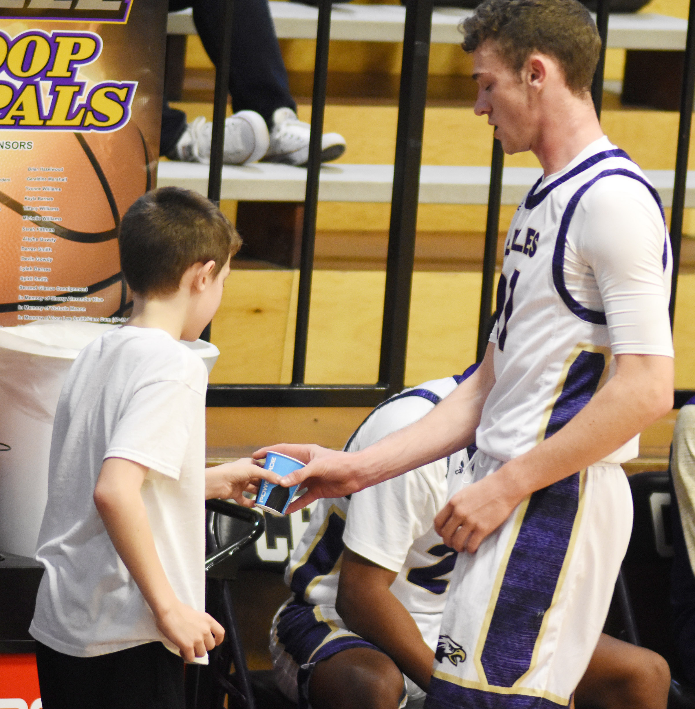 Campbellsville Elementary School third-grader Aidan Wilson gives his brother, CHS senior Connor Wilson, some water during a timeout.