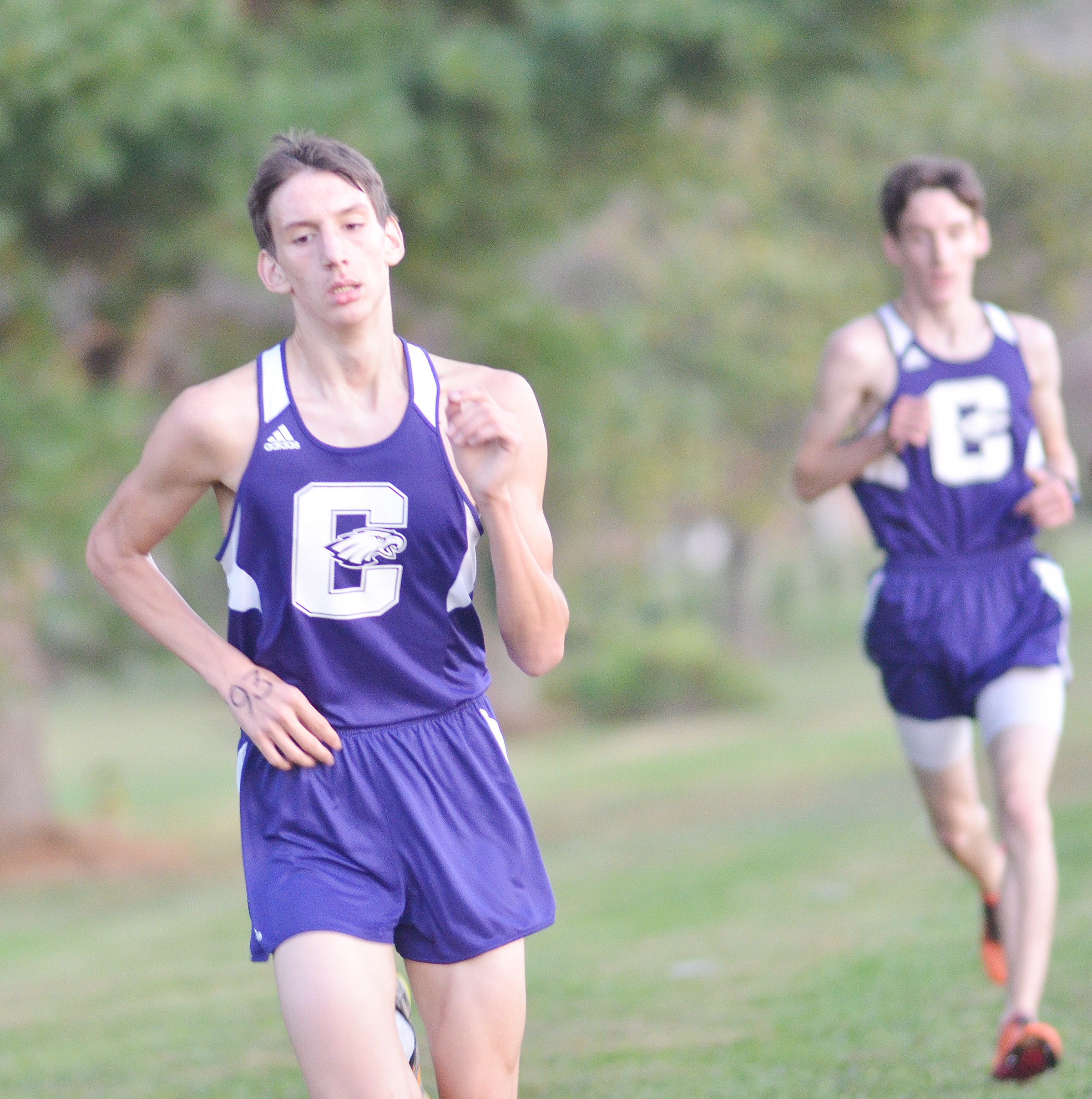 CHS junior Evan McAninch runs, as his twin brother Ian trails close behind.