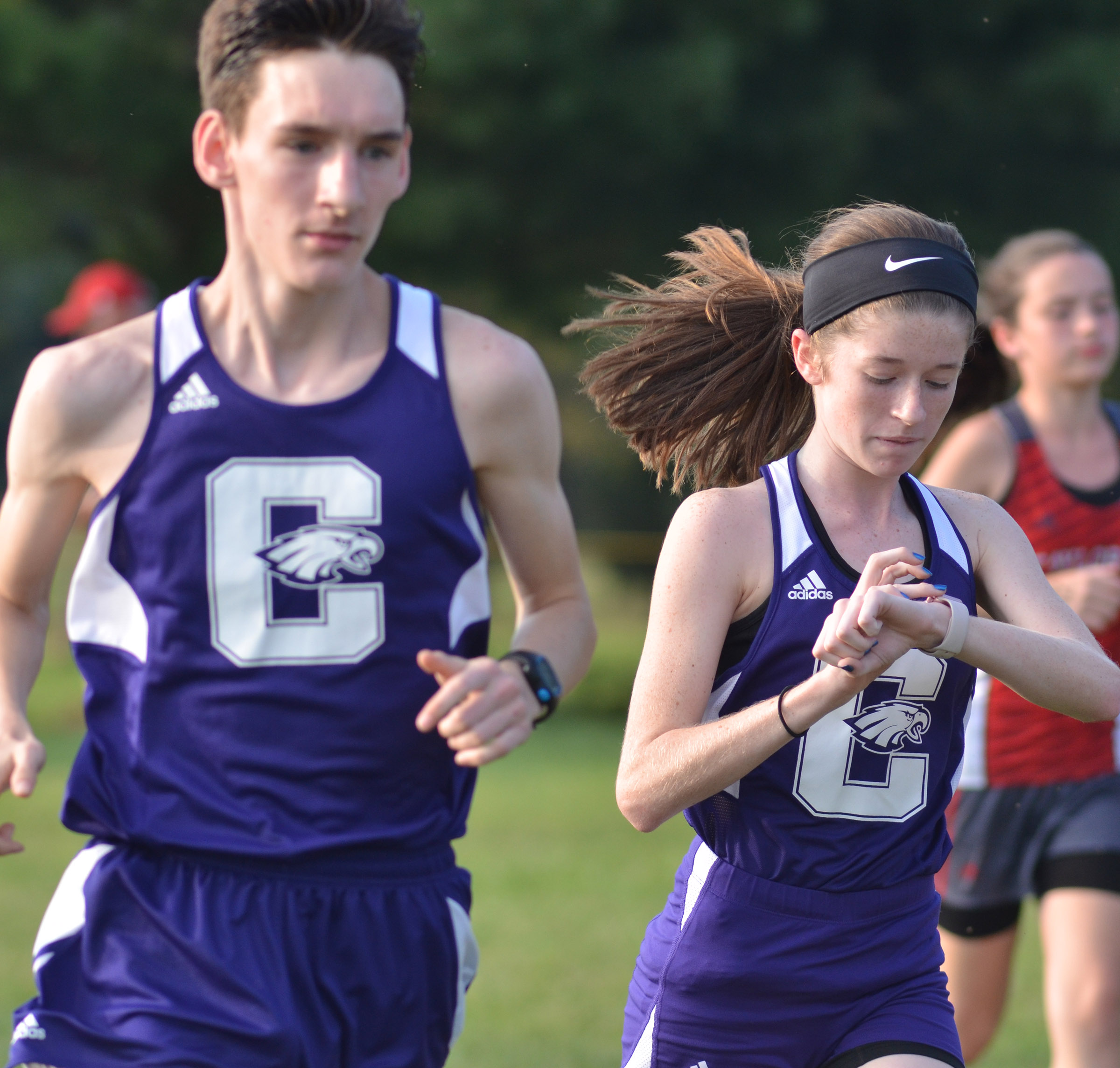 CHS sophomore Gracyne Hash sets a timer as she begins the race. At left is junior Ian McAninch.
