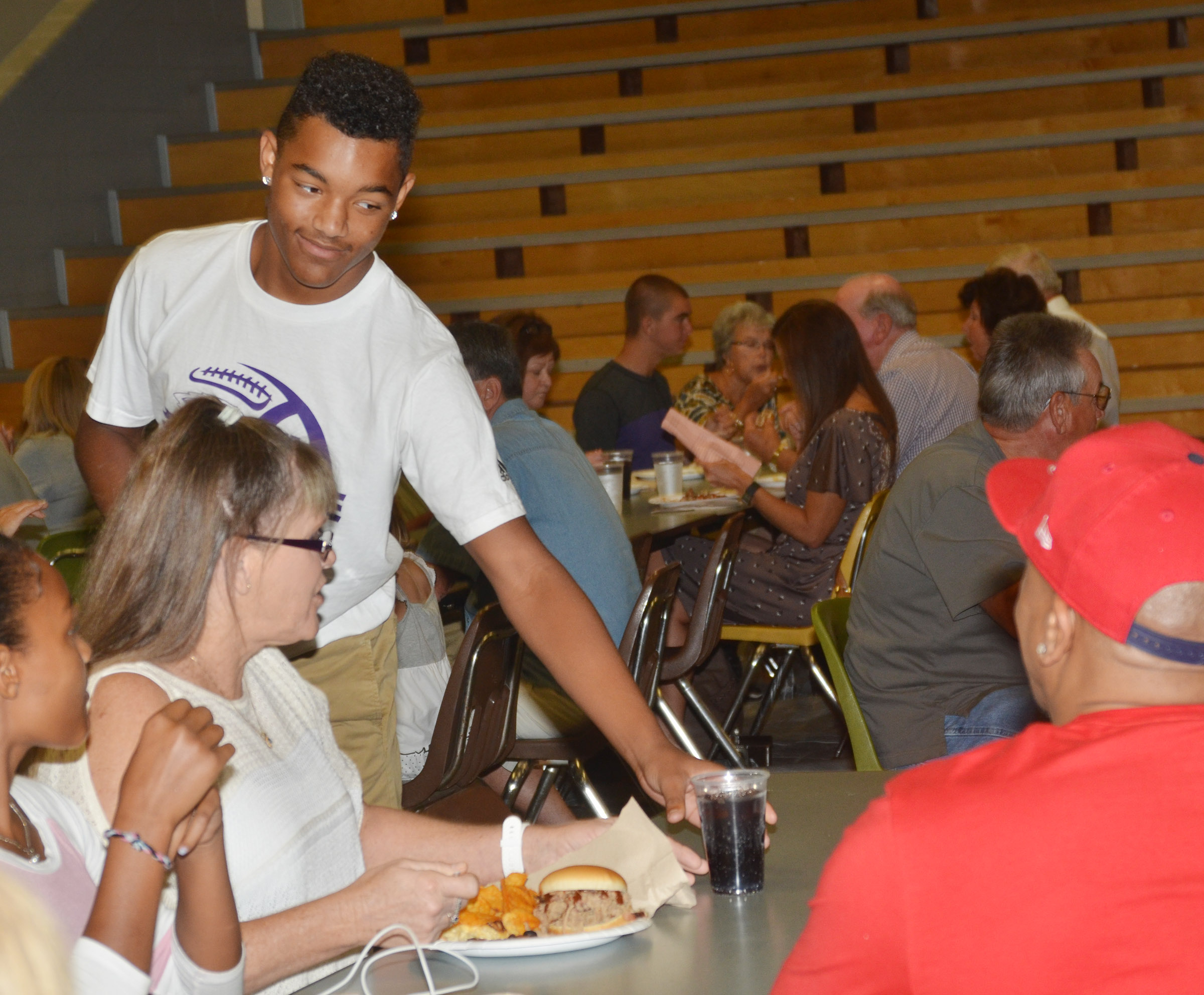 CHS freshman Reggie Thomas serves a drink at the annual CHS football dinner and auction.