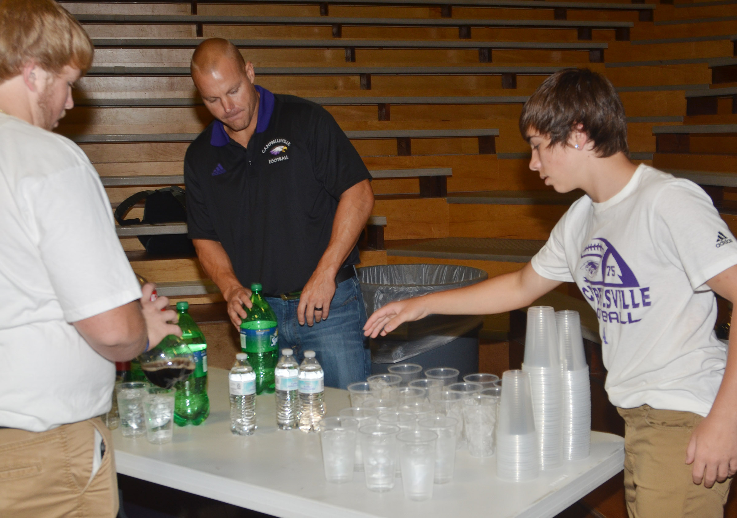CHS assistant football coach Robbie Gribbins helps seniors Ryan Jeffries, at left, and Austin Carter pour drinks at the annual CHS football dinner and auction.