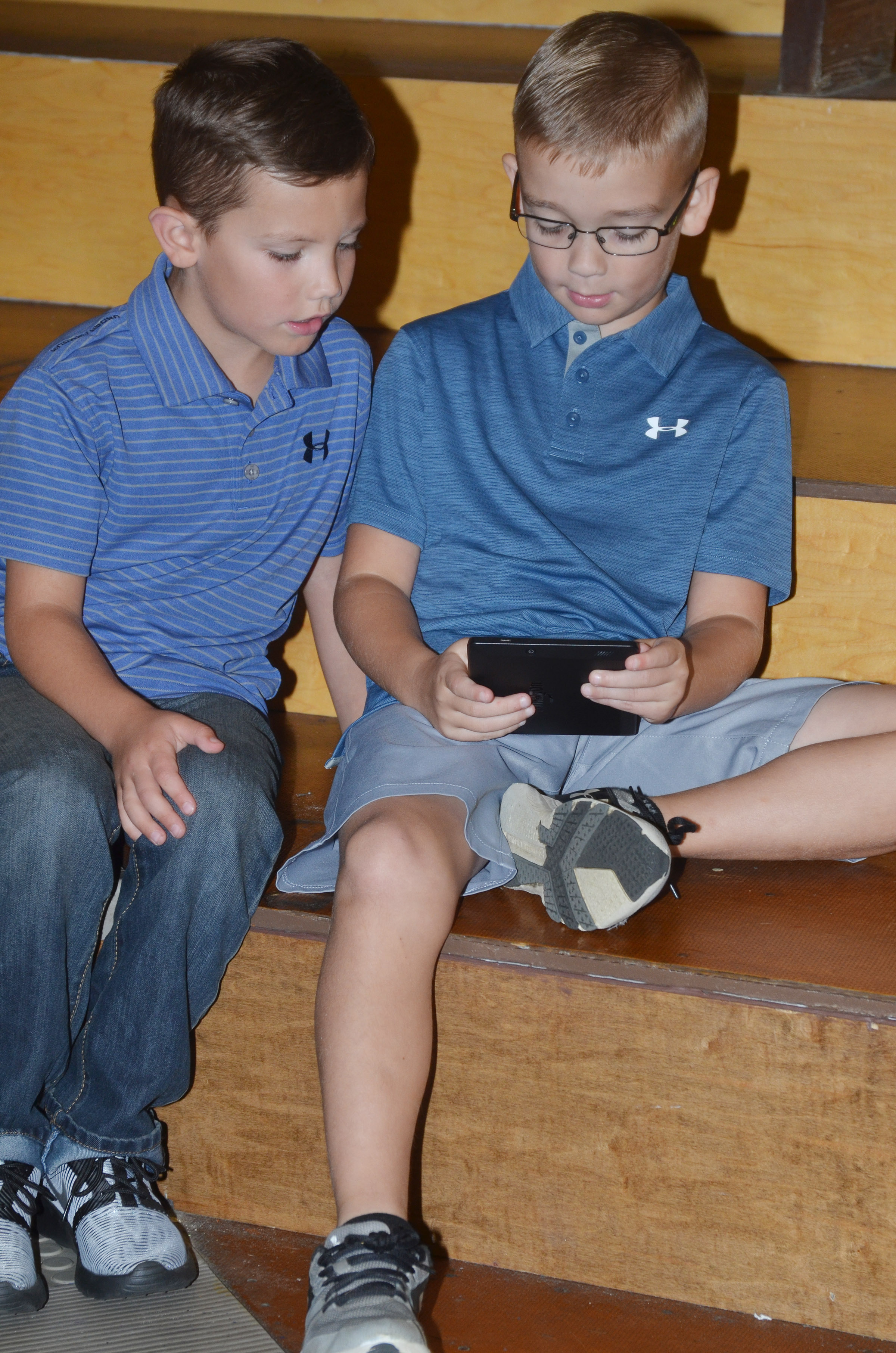 Campbellsville Elementary School second-grader Owen Skaggs, at left, and fourth-grader Cameron Estes watch videos together during the annual CHS football dinner and auction.