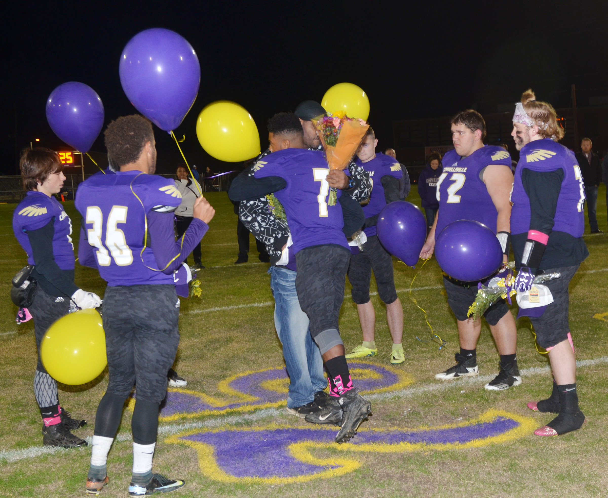 CHS senior players honor Cameron Smith, who died in 2013 and would have been a senior at CHS this year, by releasing purple and gold balloons. Smith's father William, center, attended the ceremony.