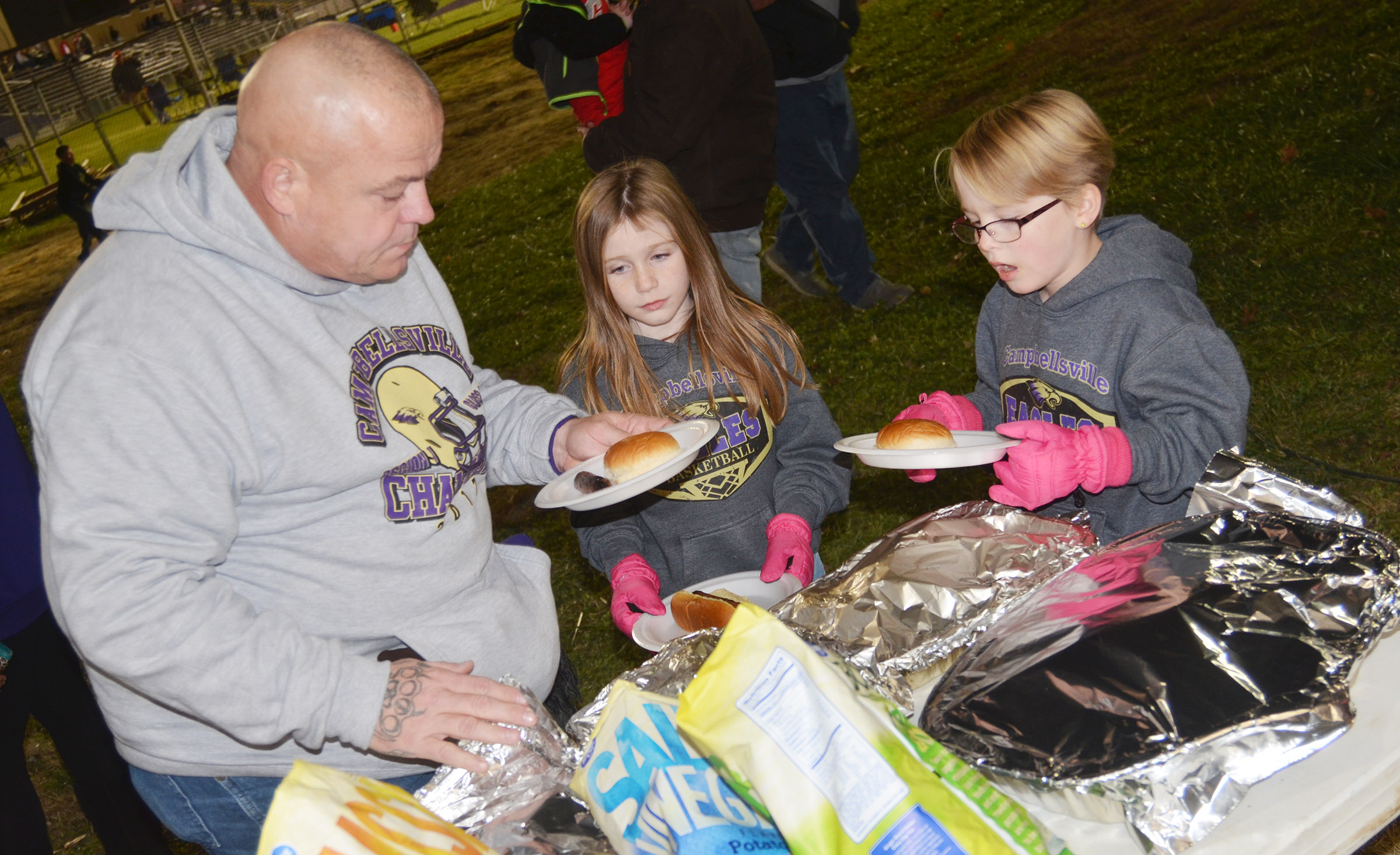 Chris Brunelle helps his daughters, CES second-graders Izzy, at left, and Maddie get their food at the tailgate.