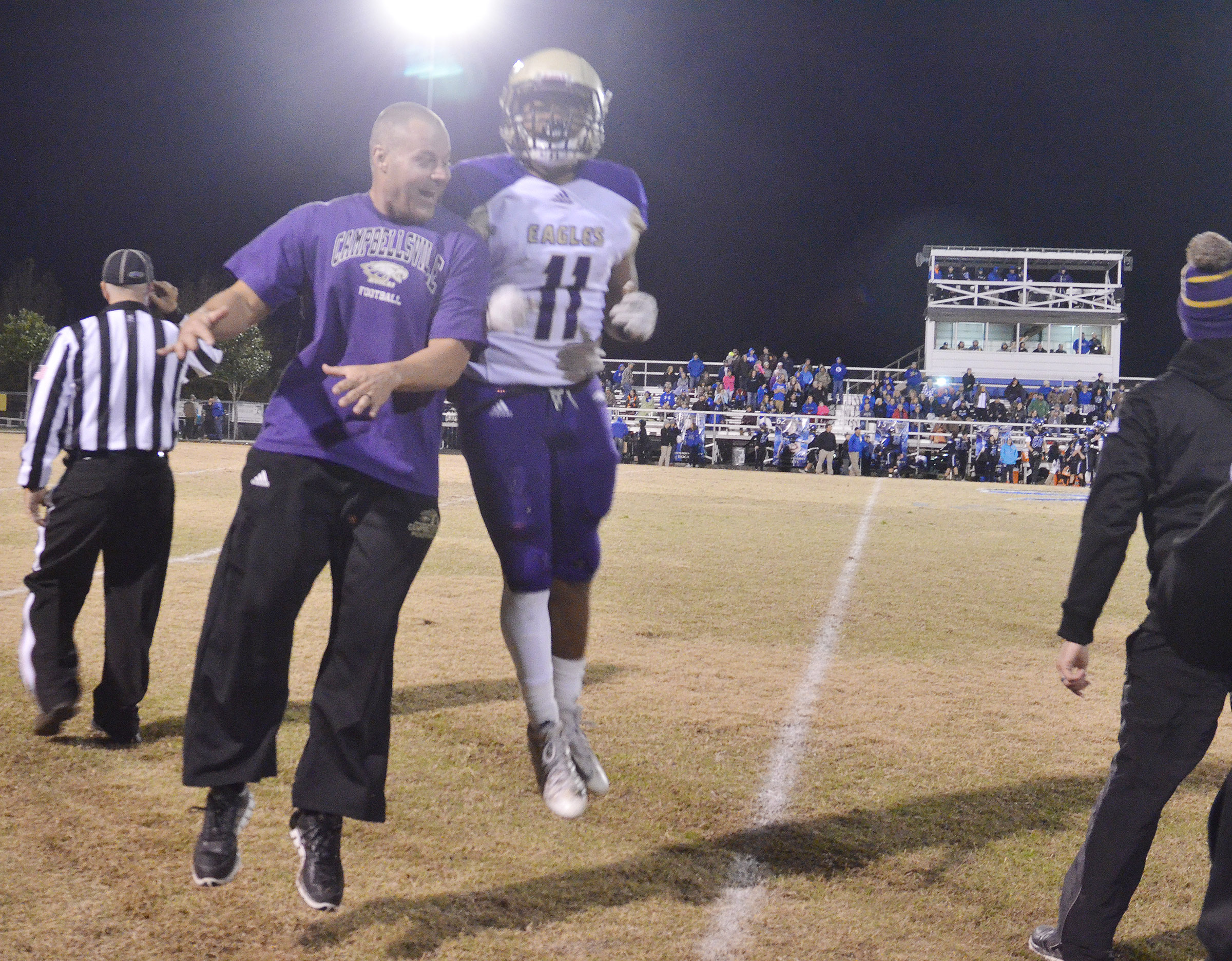 CHS assistant football coach Robbie Gribbins celebrates with sophomore Braden Paige.