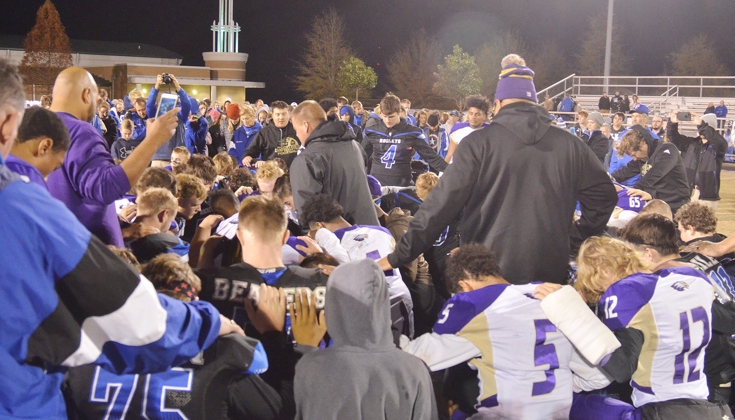 CHS head football coach Dale Estes prays with his players and coaches, along with Crittenden County players and coaches.