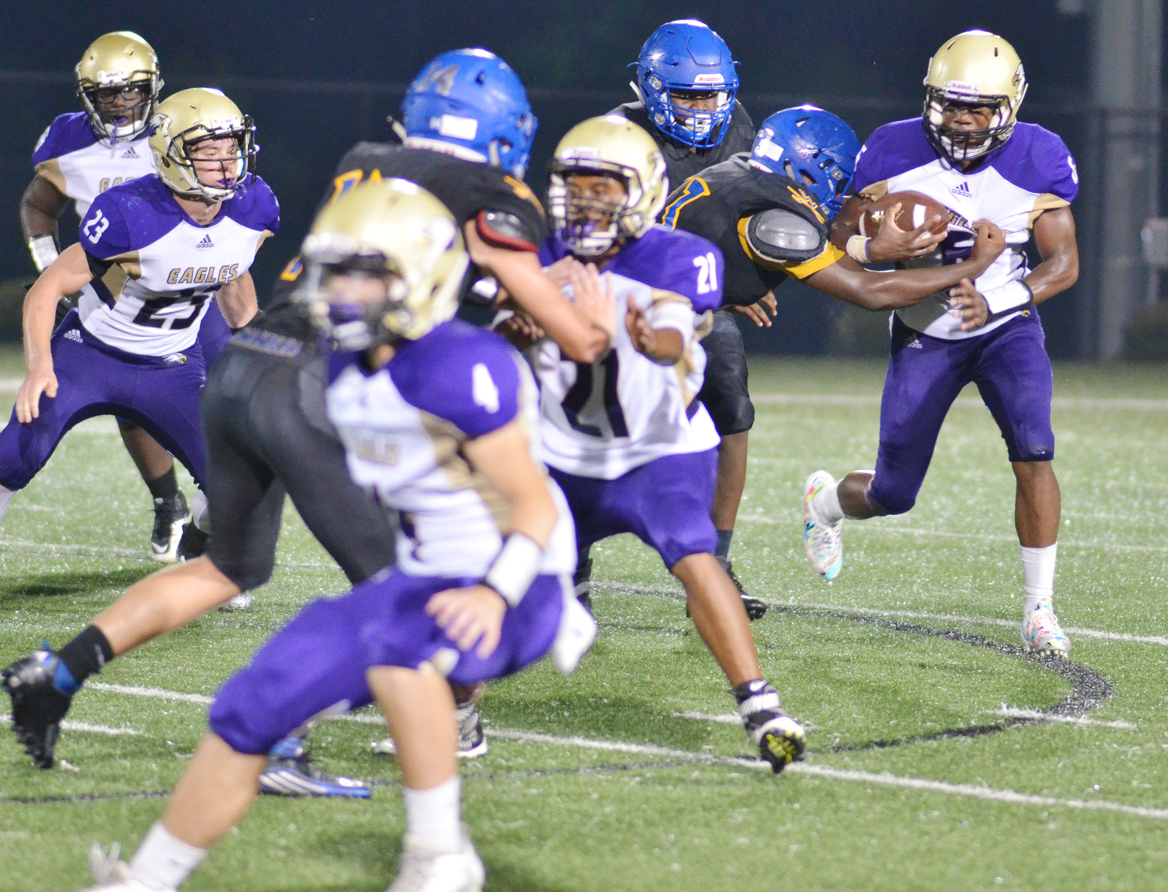 CHS sophomore Malachi Corley runs the ball as his teammates block.