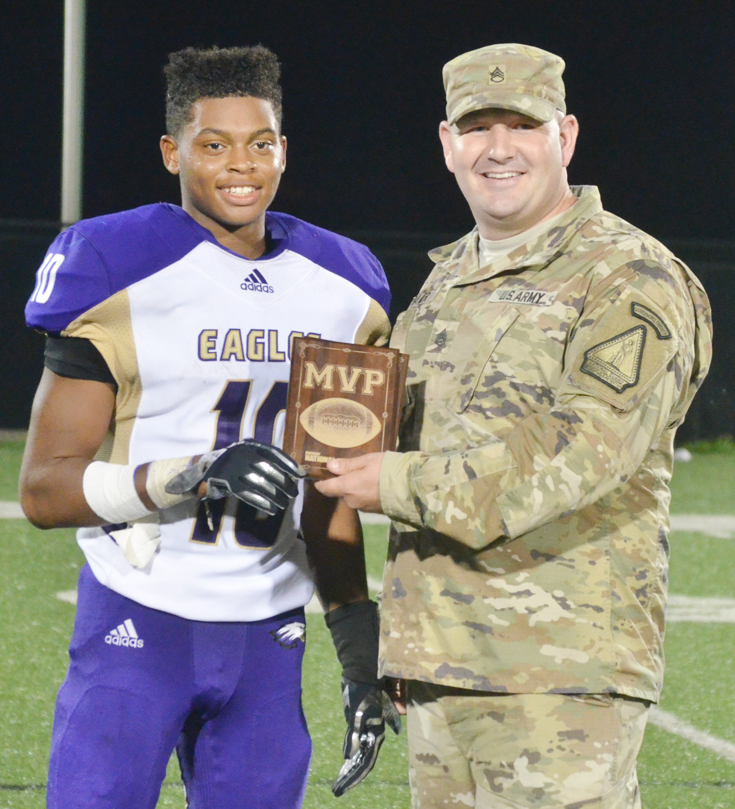 CHS senior Devonte Cubit receives the National Guard player of the game plaque from Staff Sgt. Phillip Baker.