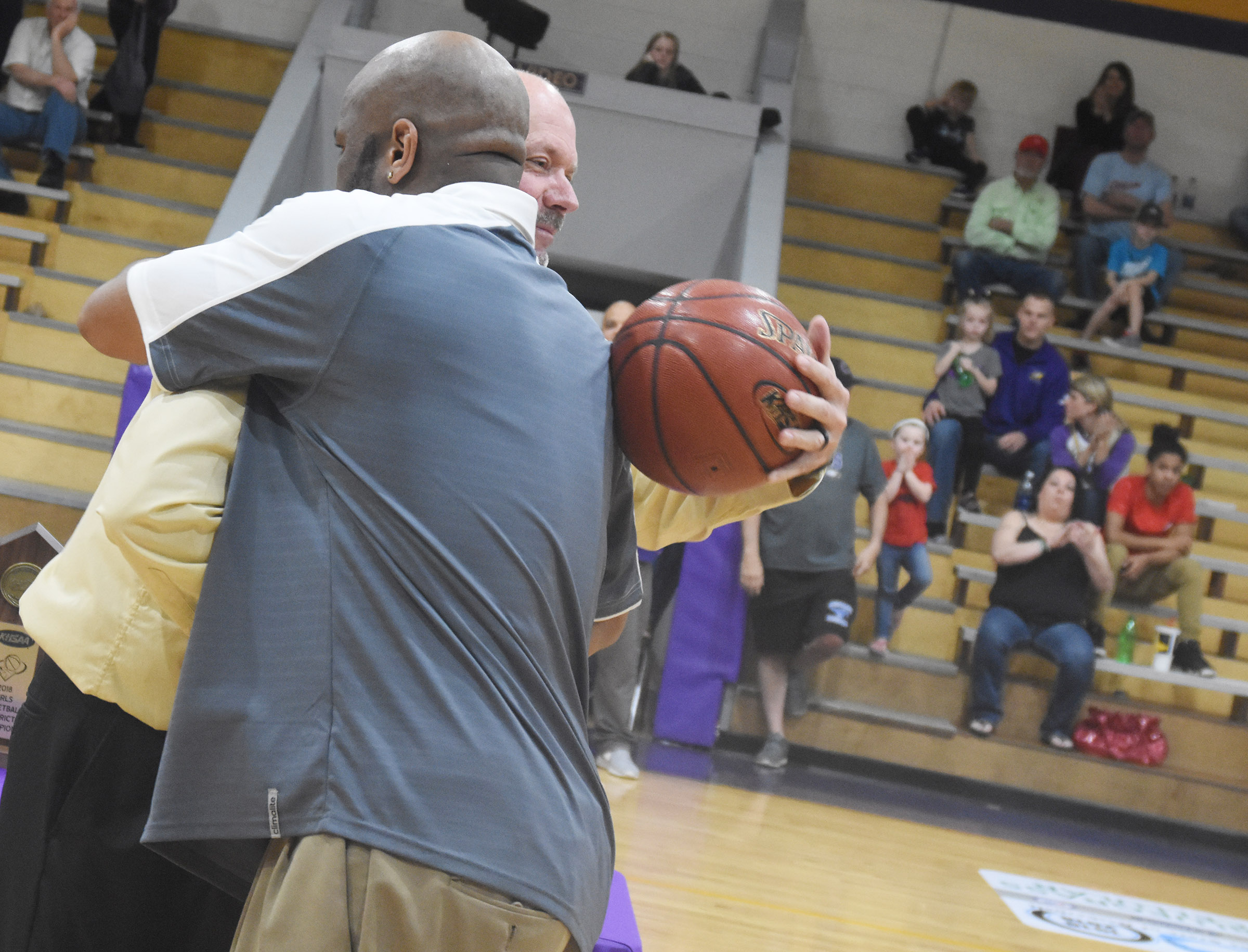 CHS girls' basketball head coach Anthony Epps receives the game ball from CHS Athletic Director Tim Davis.