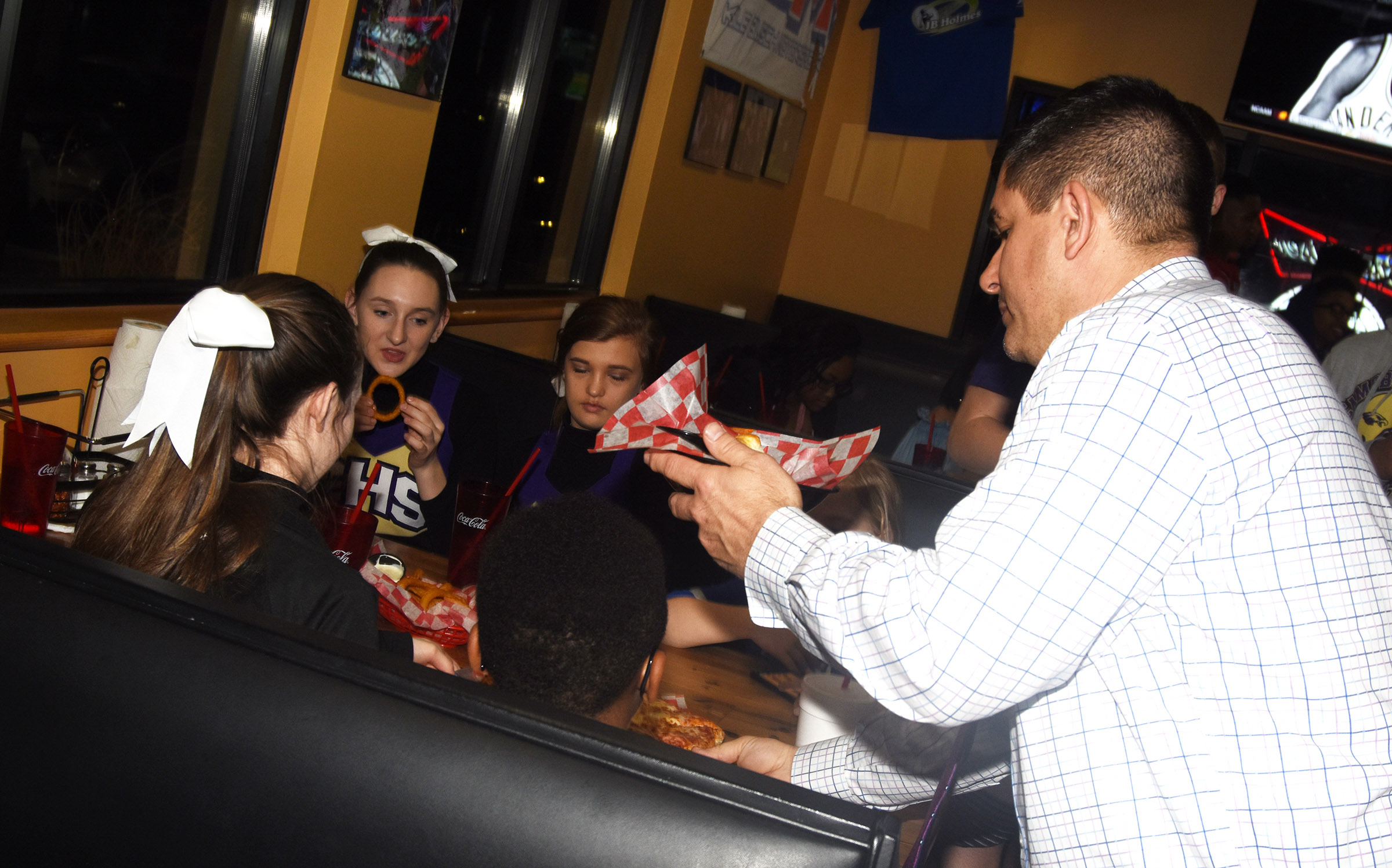 Campbellsville Independent Schools Superintendent Kirby Smith congratulates the CHS girls' basketball team during a celebration at Wings, Pizza N Things.