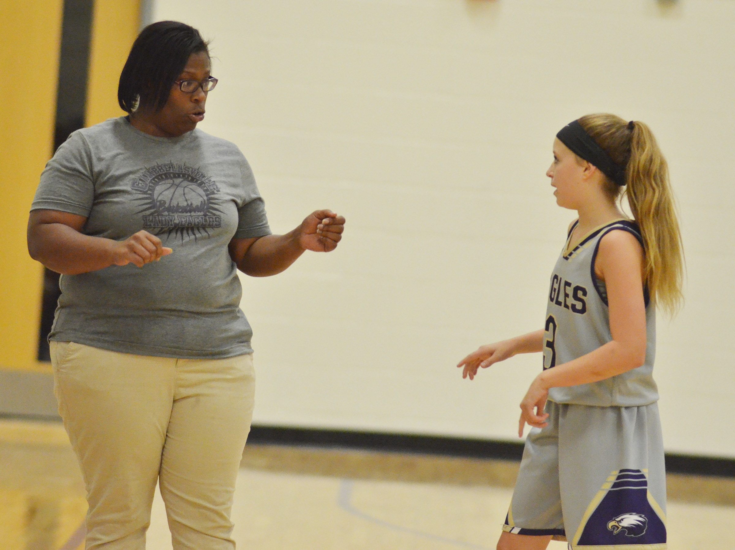 CMS girls' basketball head coach Tiarra Cecil talks with eighth-grader Rylee Petett during a time out.