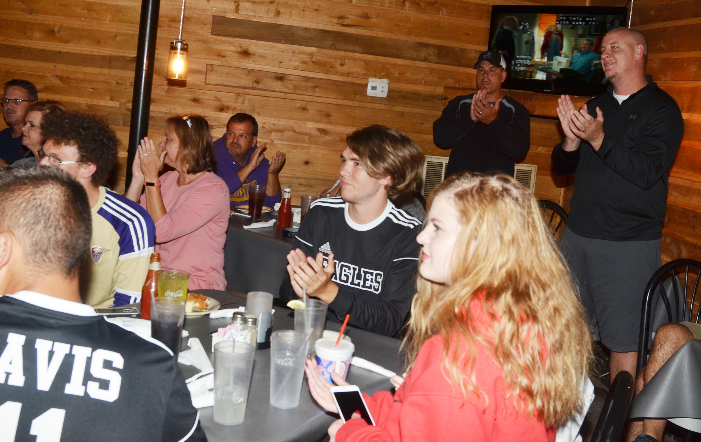 Campbellsville Independent Schools Superintendent Kirby Smith, in back, at left, and CHS Principal David Petett cheer as the team celebrates at Creek Side Restaurant.