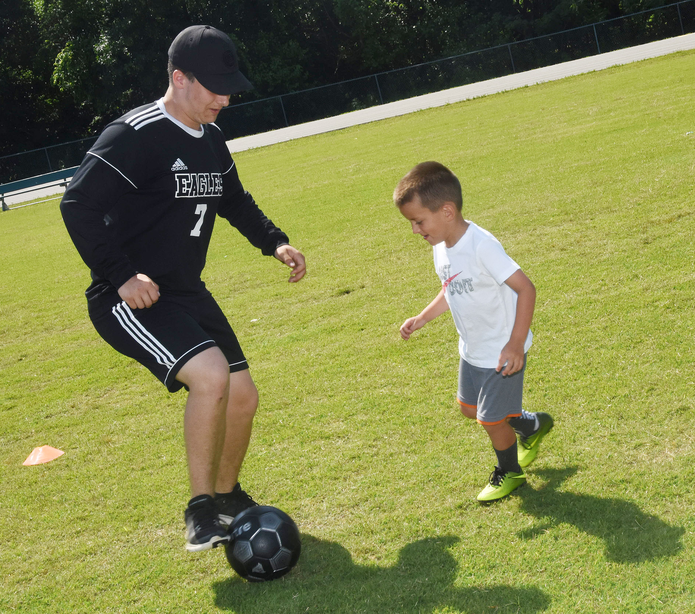 CHS senior and soccer player Brody Week leads a drill with Will Davis.