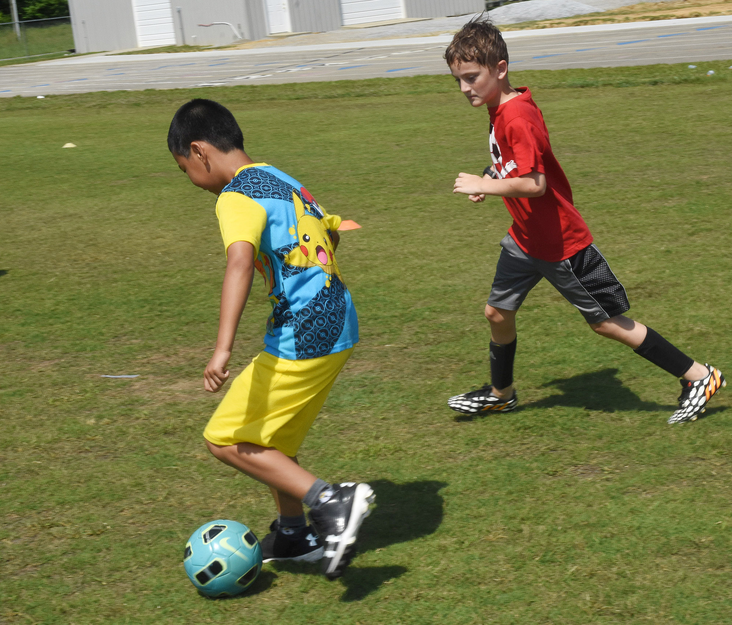Campbellsville Elementary School fourth-grader Alfie Su, at left, and CES fifth-grader Noah Leachman compete for the ball.