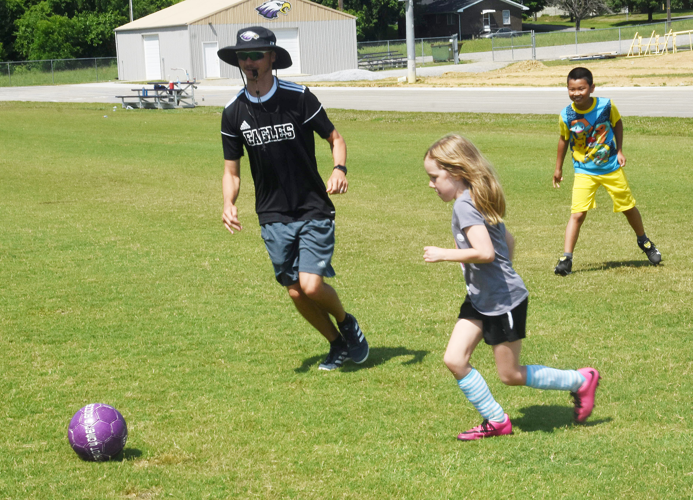 CHS head soccer coach Bradley Harris leads a drill with campers Athena Angel, at left, and Campbellsville Elementary School fourth-grader Alfie Su.