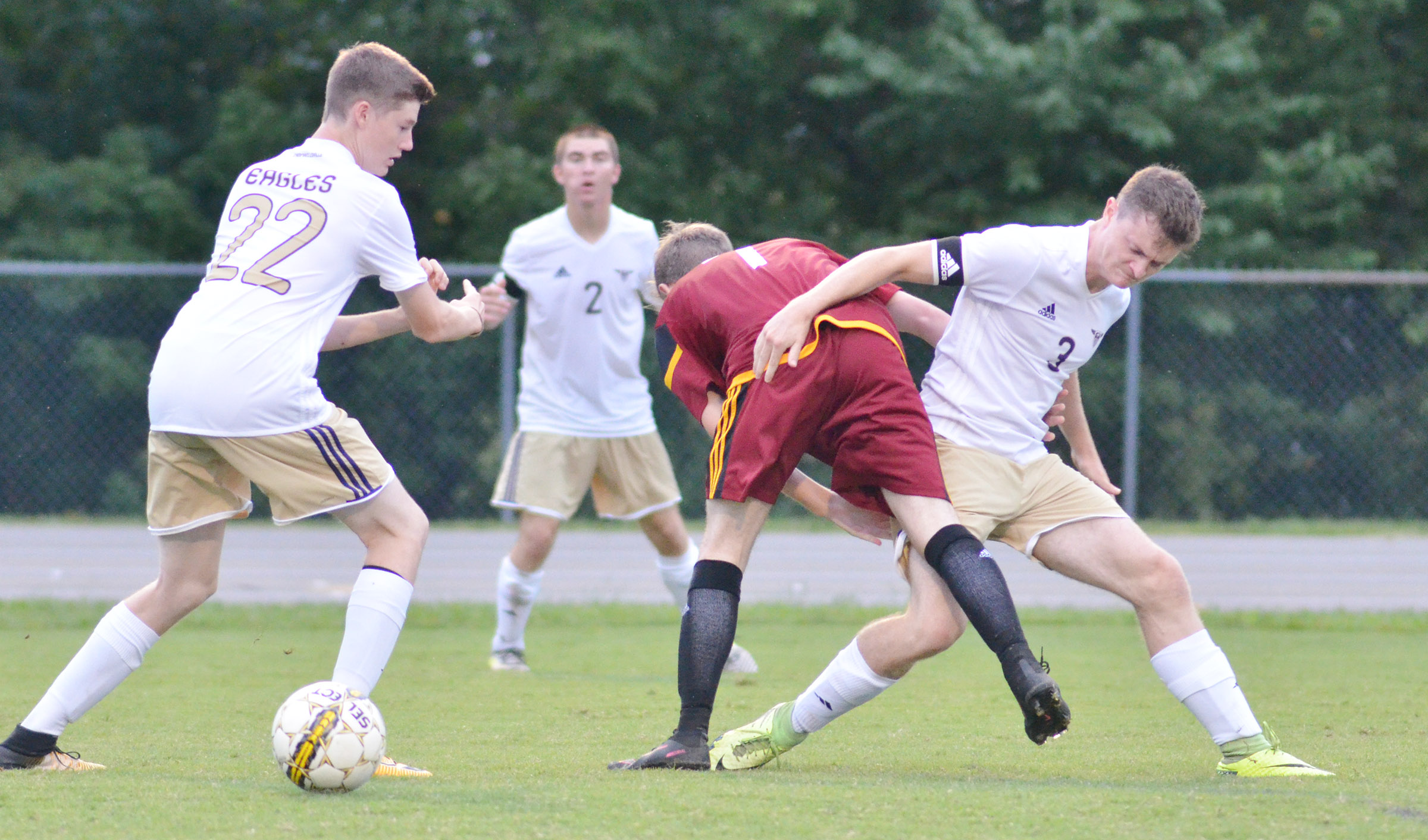 CHS senior Bryce Richardson battles a Garrard County defender as freshman Tristin Faulkner gets the ball.