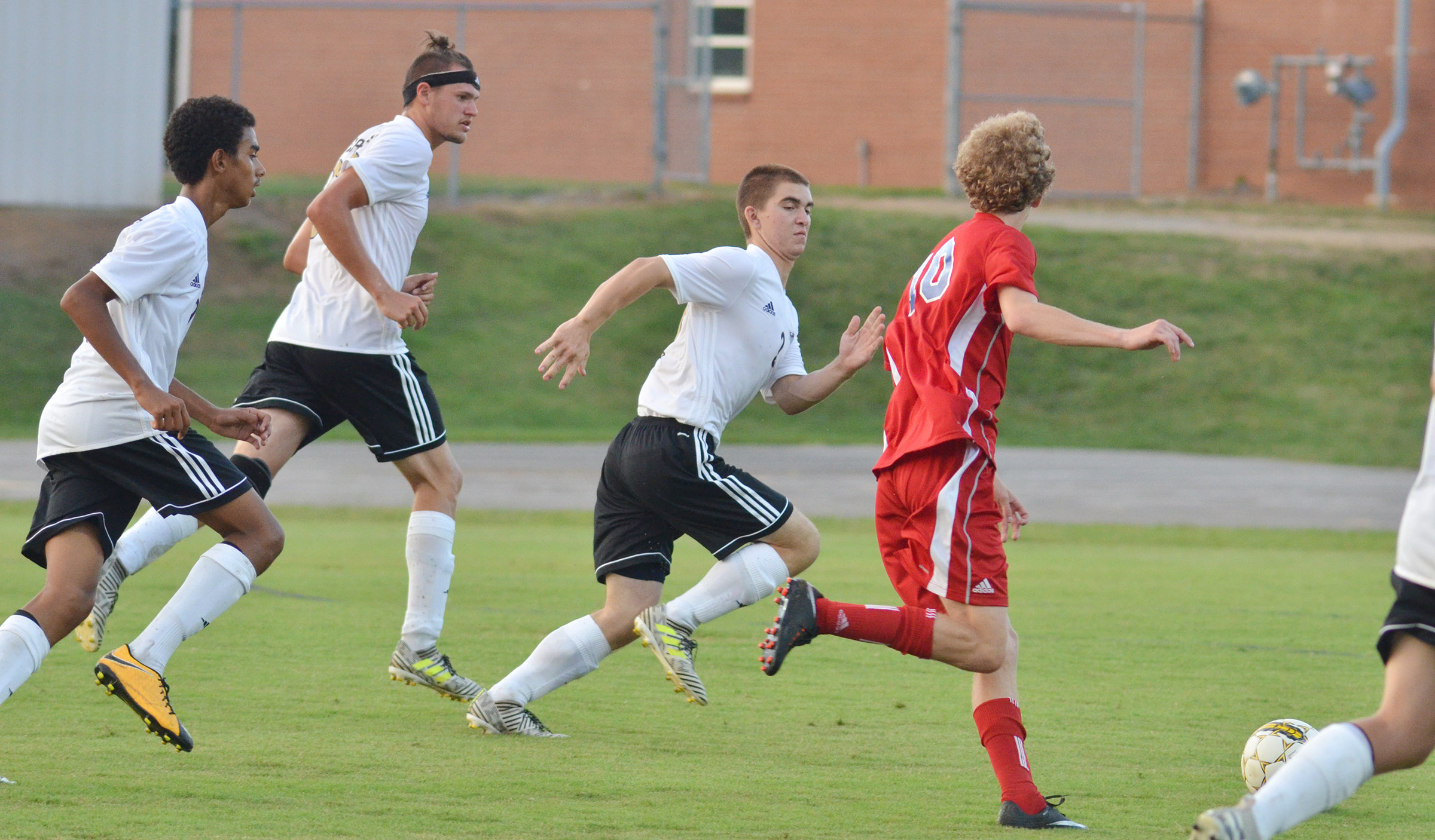 From left, CHS sophomore David Silva and seniors Logan Cole and Cass Kidwell run to the ball.
