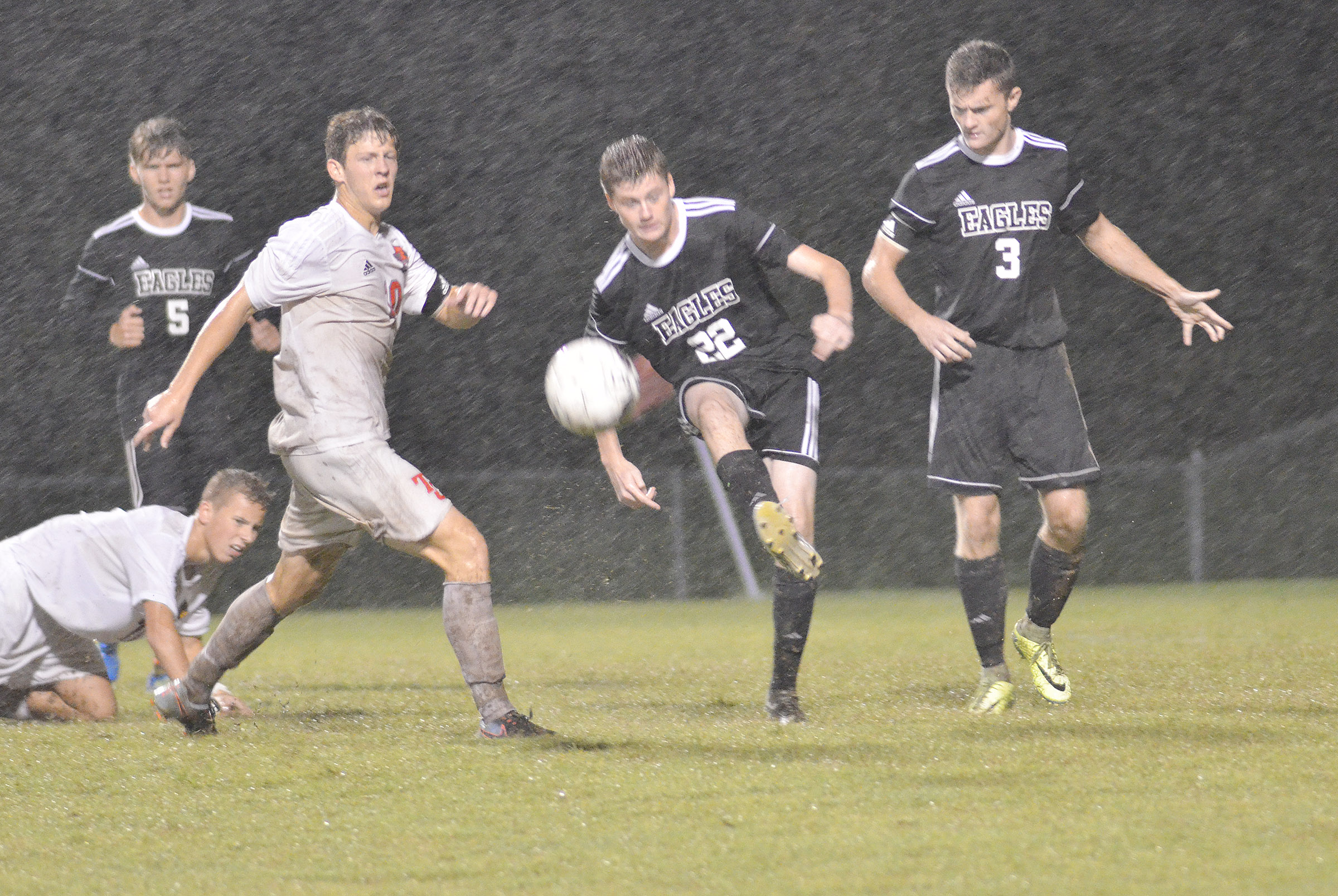 CHS freshman Tristin Faulkner kicks the ball as teammates Christian Berry, at left, a senior, and senior Bryce Richardson play defense.