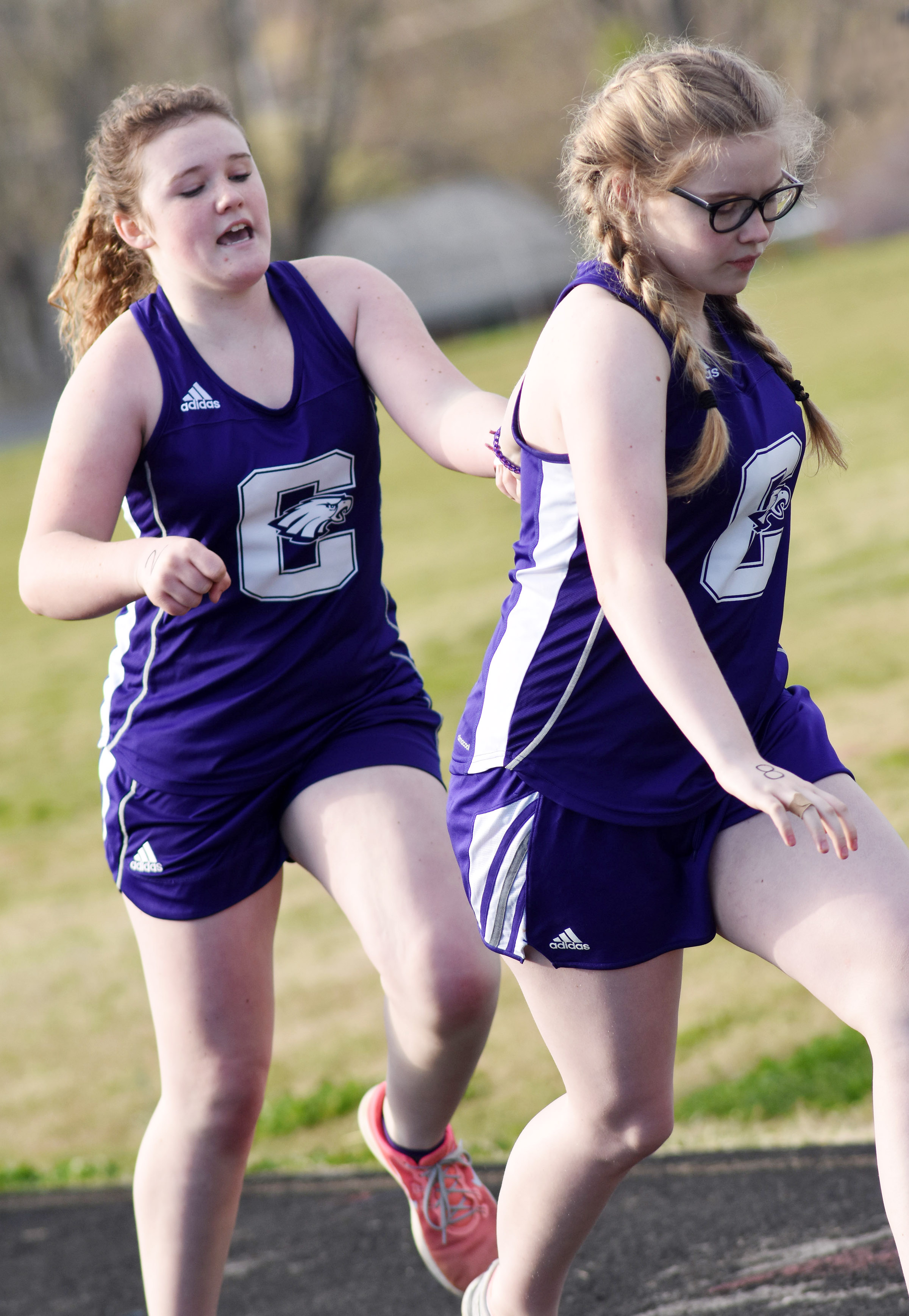 Campbellsville Middle School eighth-grader Abby Brisko, at left, hands the baton to seventh-grader Whitney Frashure.