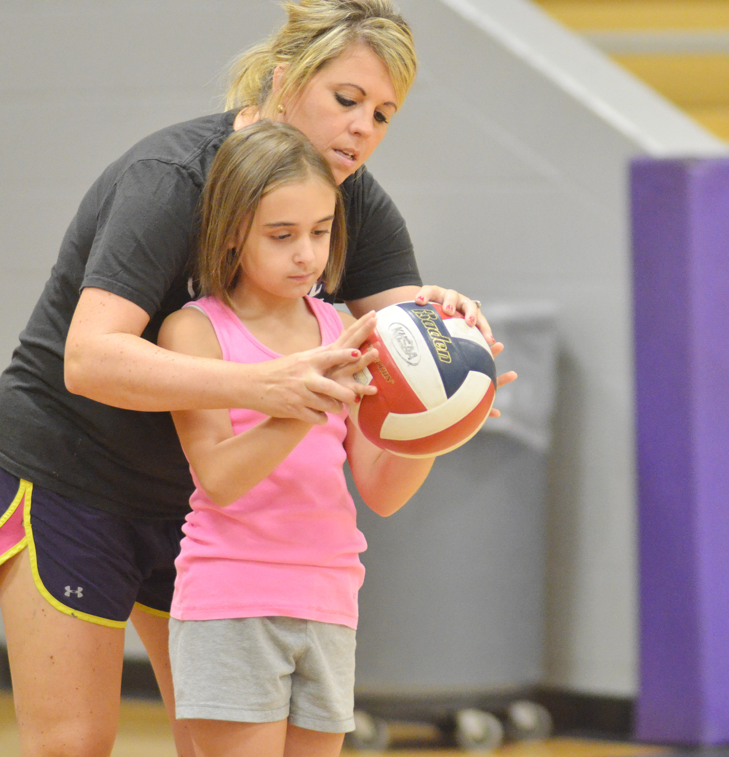 CHS head volleyball coach Elisha Rhodes helps CES fifth-grader Anna Floyd learn to serve.