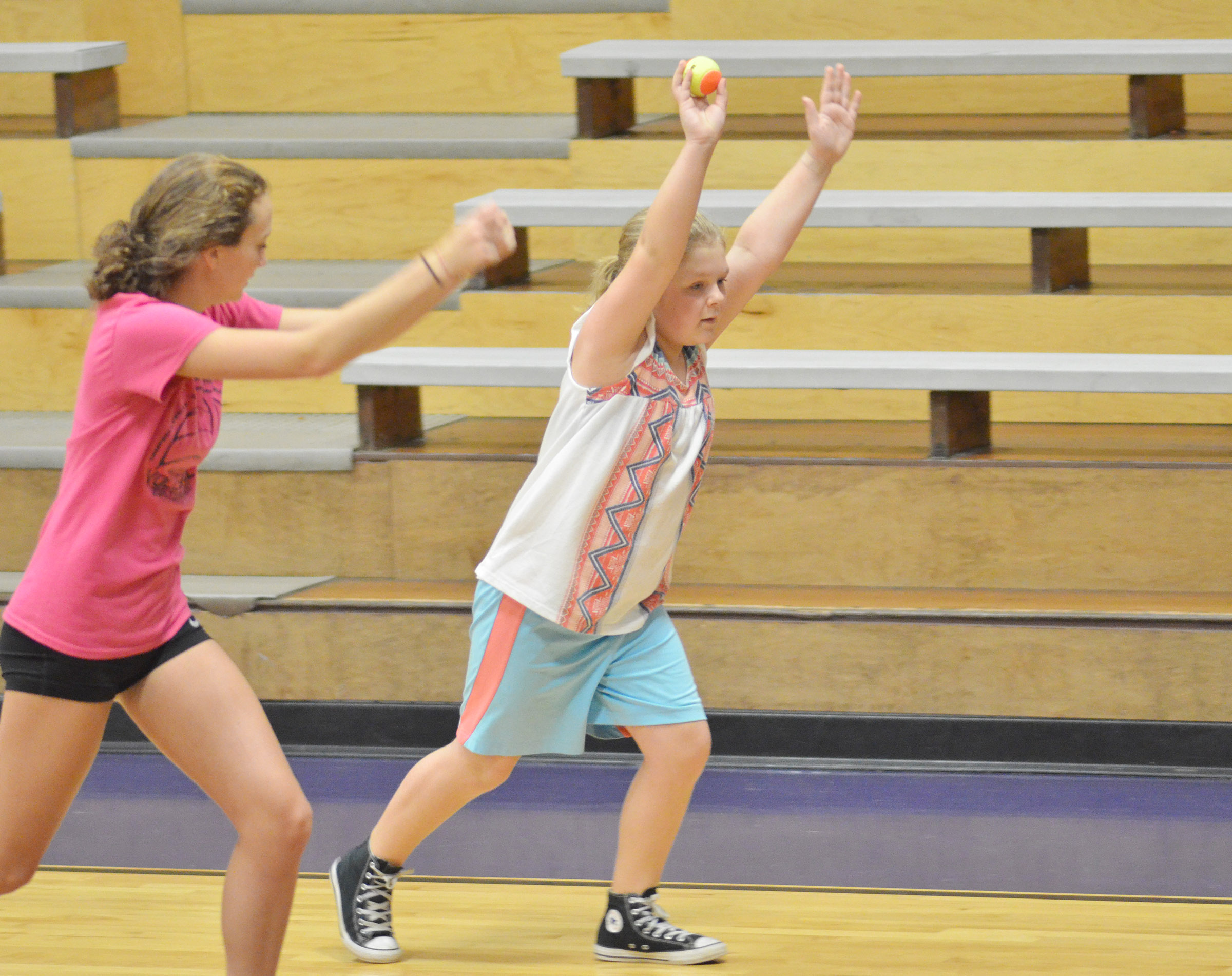 CHS junior Salena Ritchie helps CMS sixth-grader Alexis Sharp do a drill.