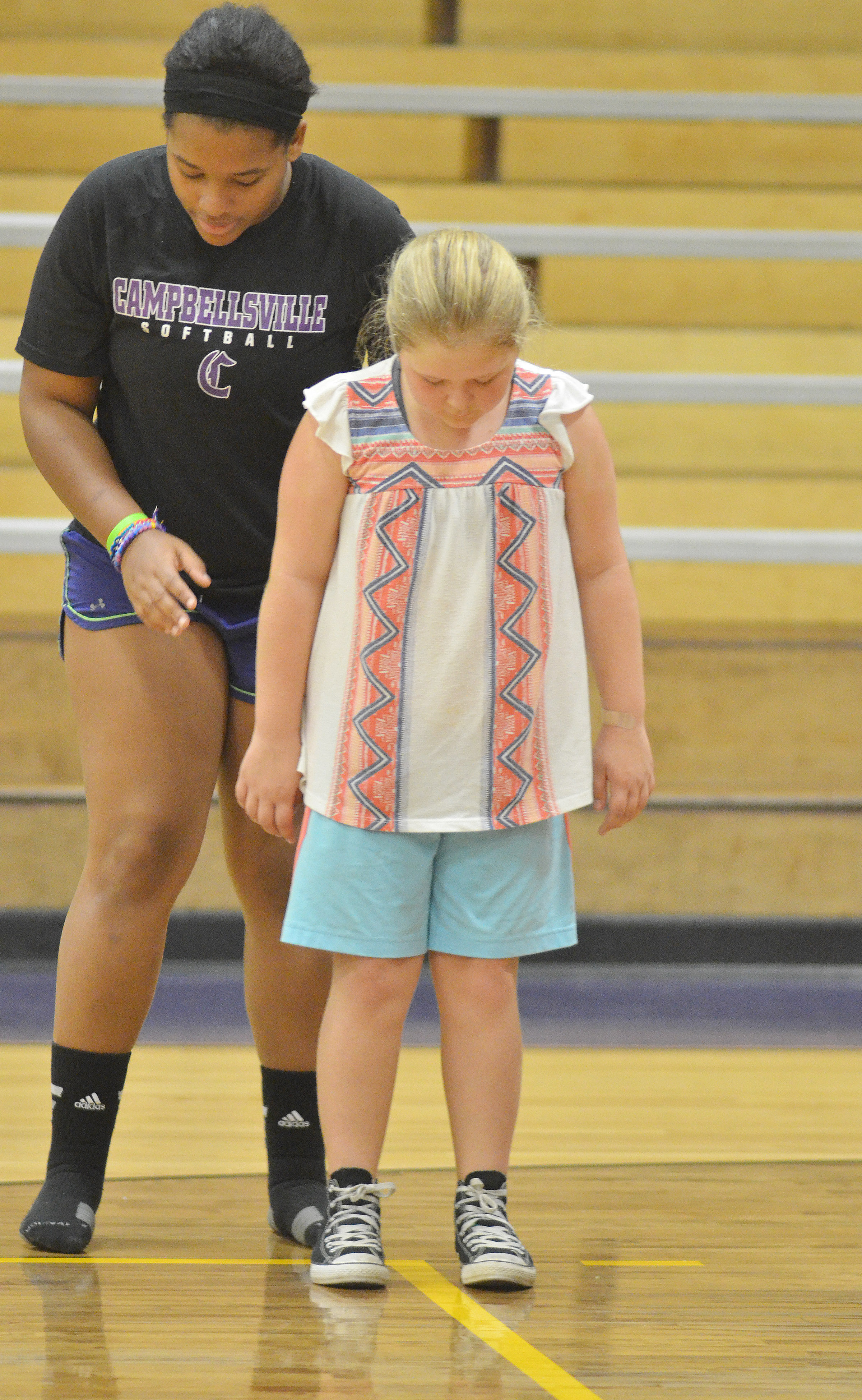 CHS senior Kayla Young helps CMS sixth-grader Alexis Sharp with a drill.