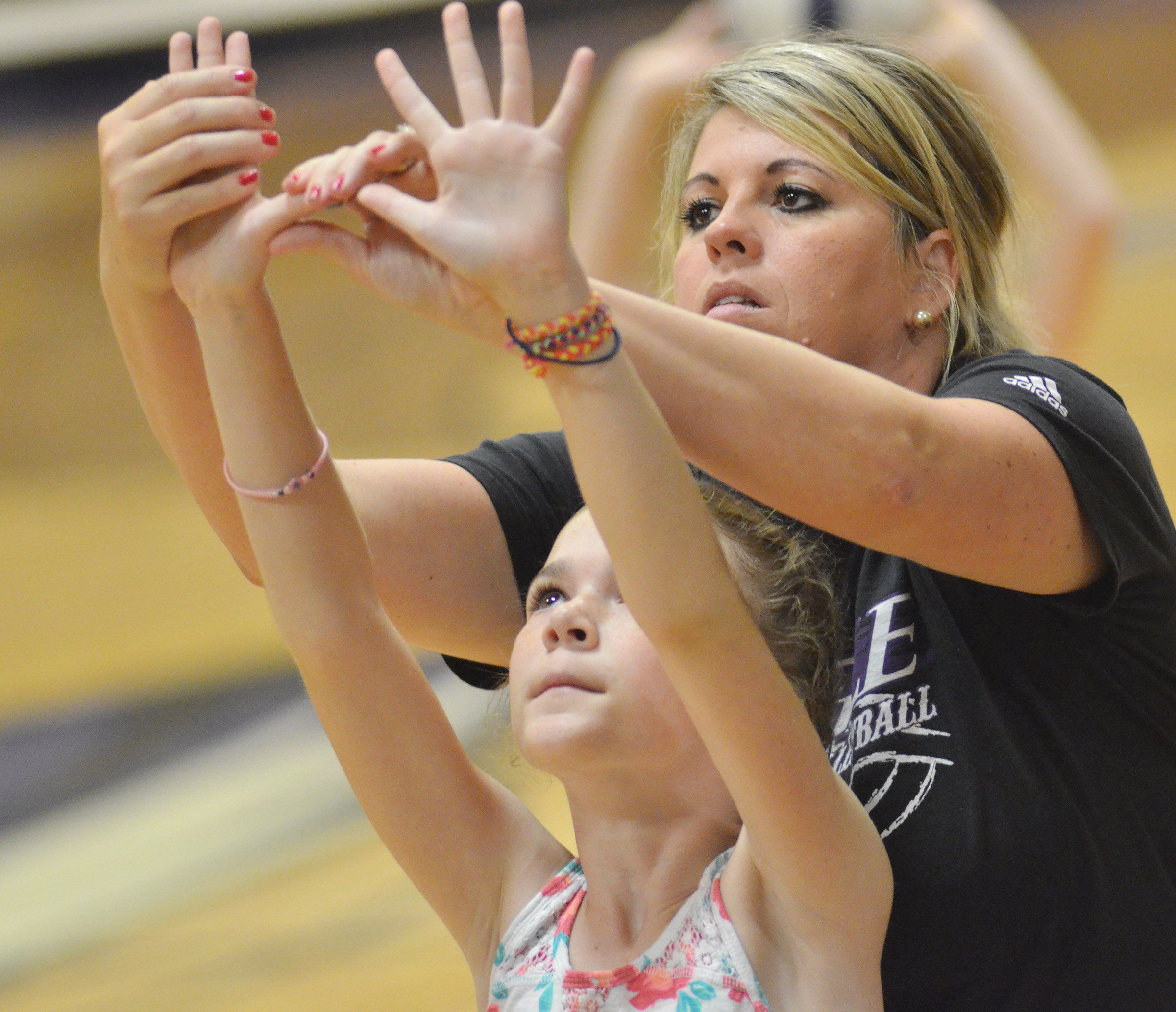 CHS head volleyball coach Elisha Rhodes helps Alissa Hughes, a fourth-grader at Hodgenville Elementary School, learn to serve.