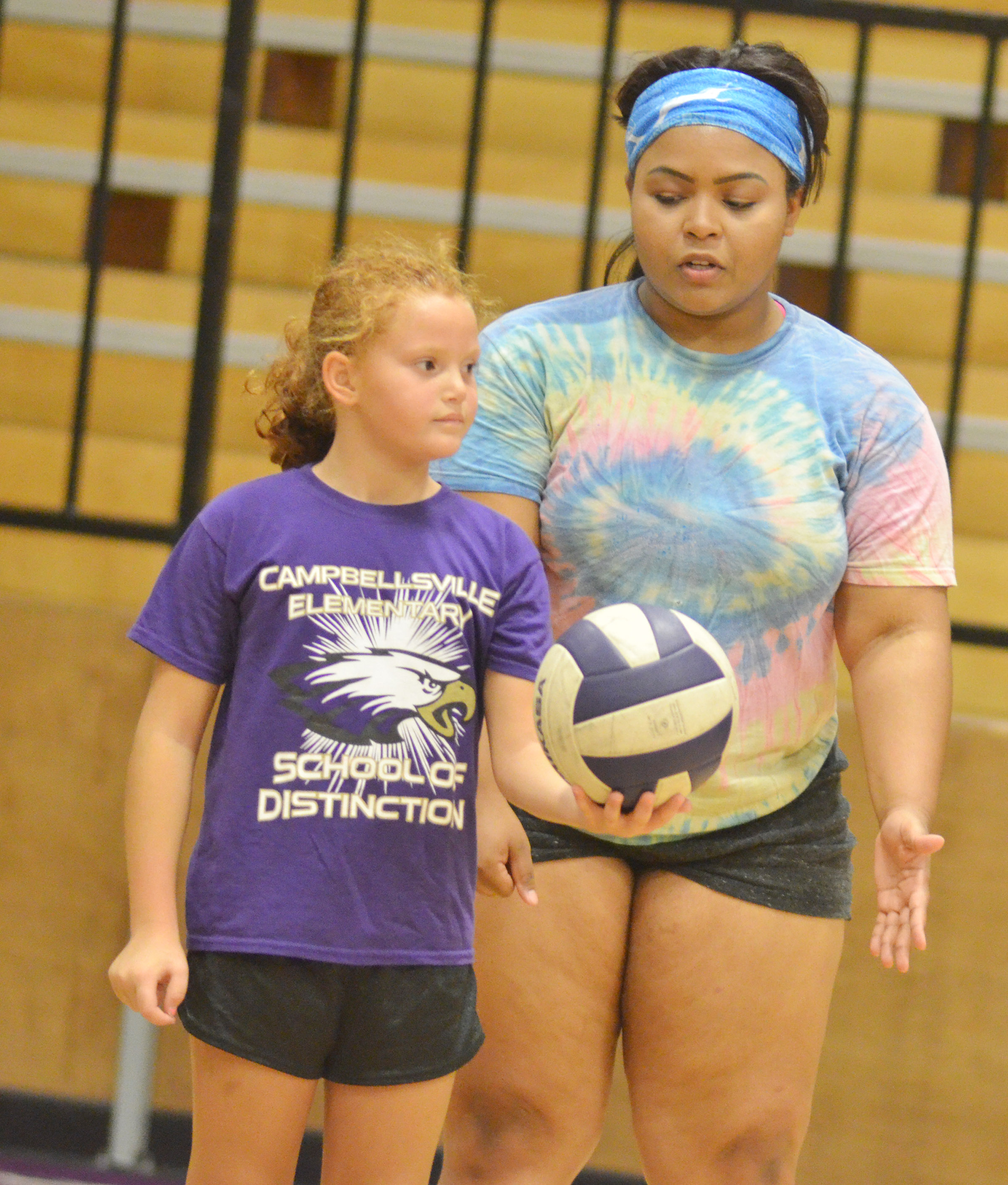 CHS junior Natalie Caldwell helps third-grader Analeigh Foster serve.