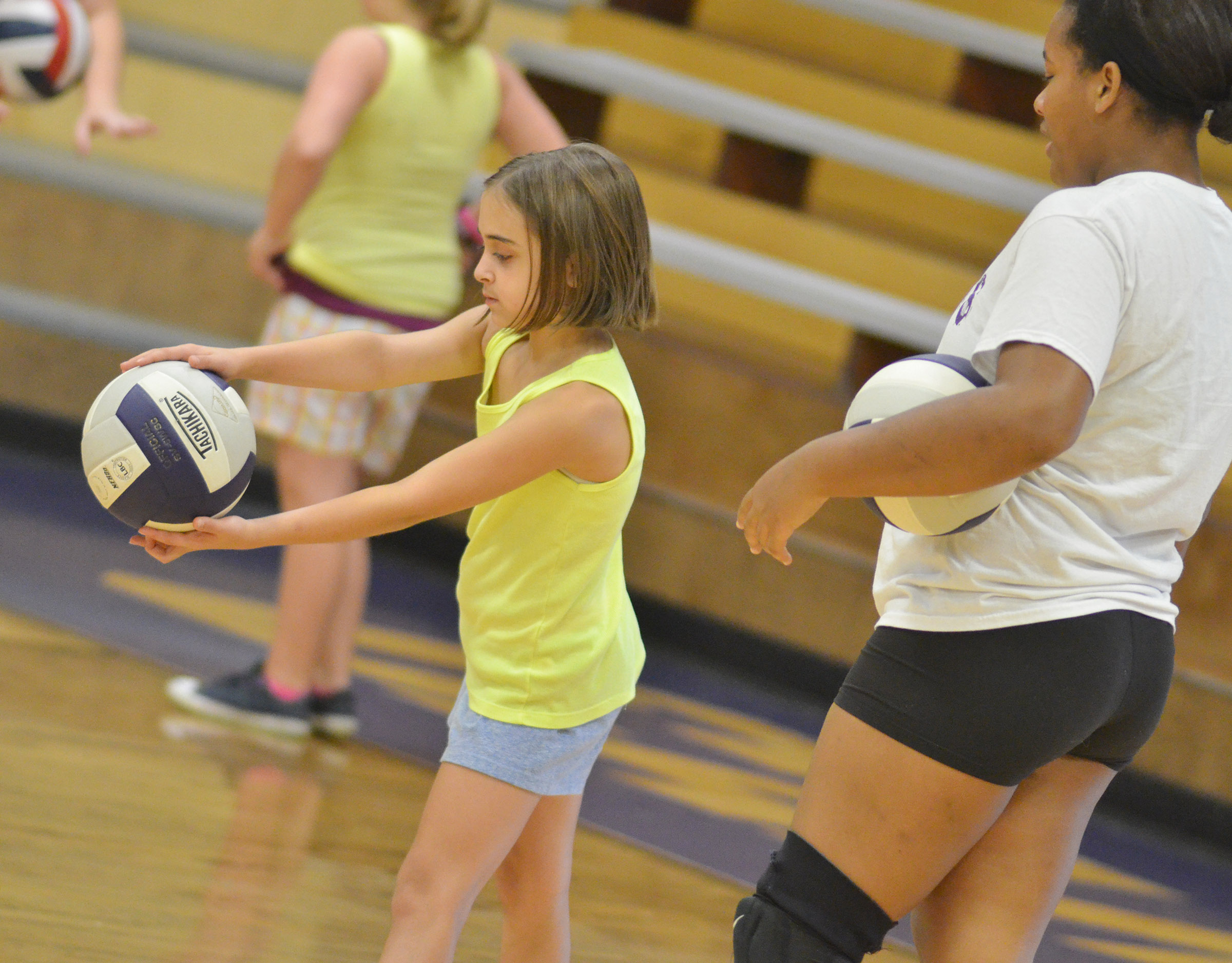 CHS senior Kayla Young helps CES fifth-grader Anna Floyd with her serve.
