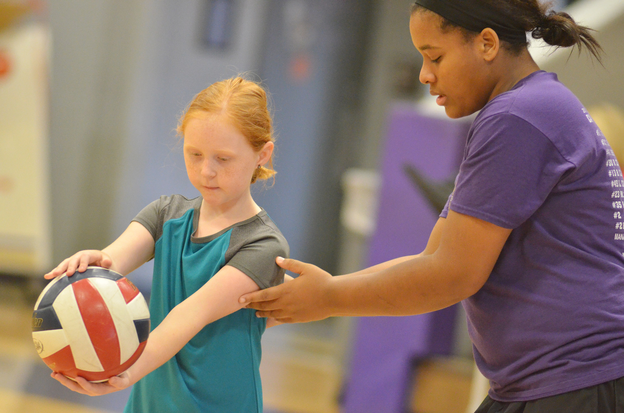 CHS senior Kayla Young helps CES fourth-grader Nora Harris learn to serve.