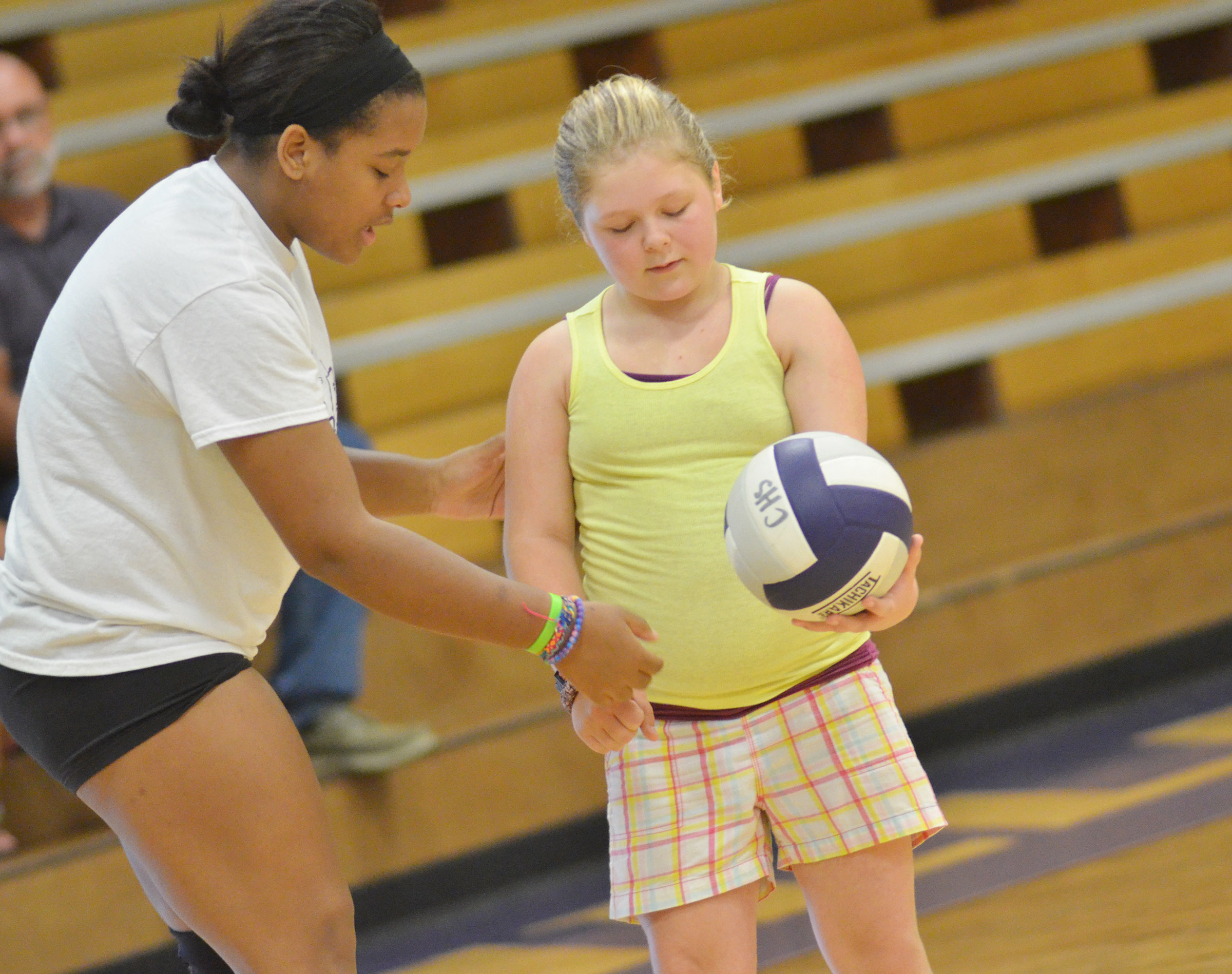 CHS senior Kayla Young talks to CMS sixth-grader Alexis Sharp about the correct way to serve.