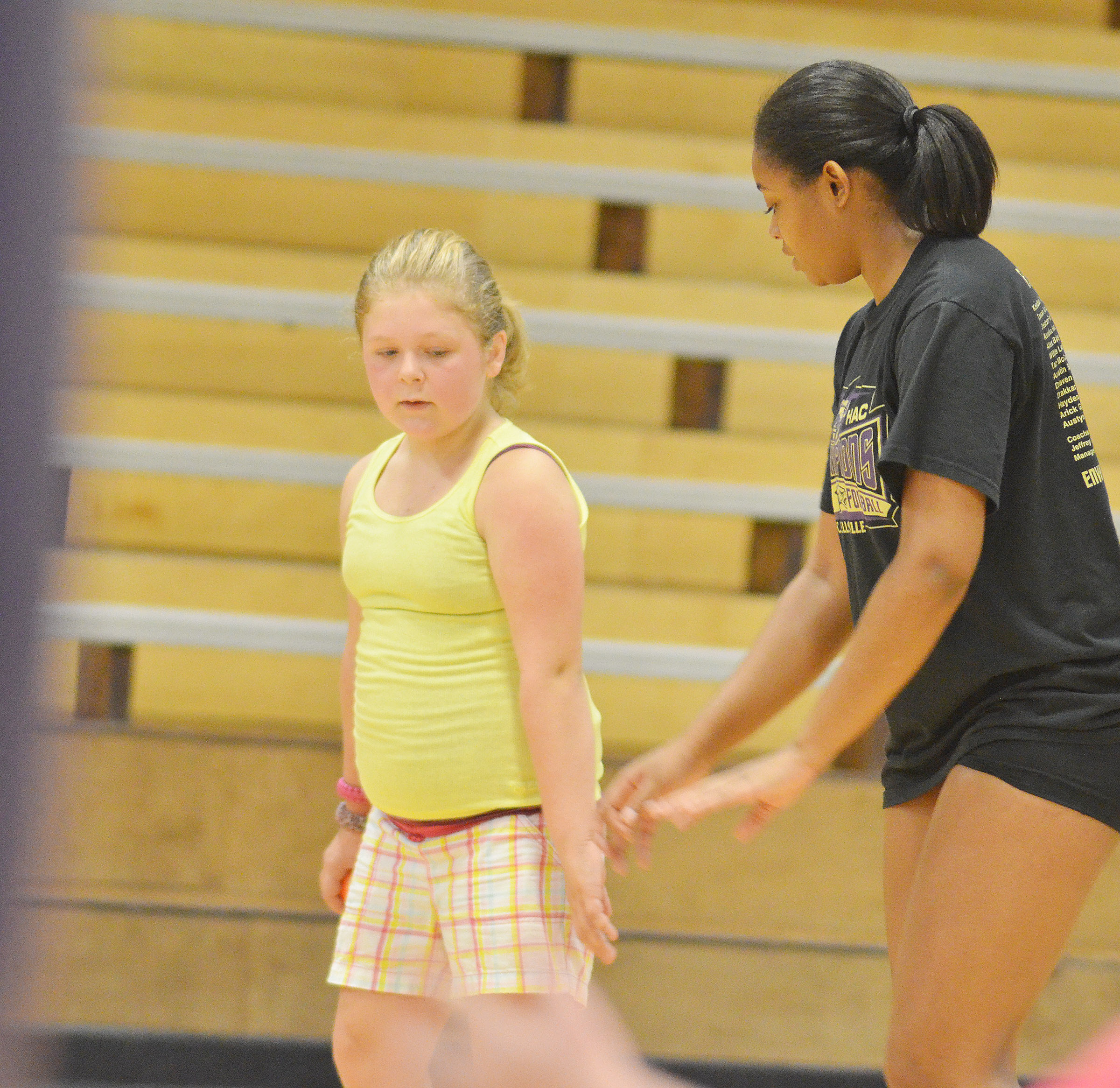 CHS senior Vonnea Smith helps CMS sixth-grader Alexis Sharp learn how to jump and hit the ball.