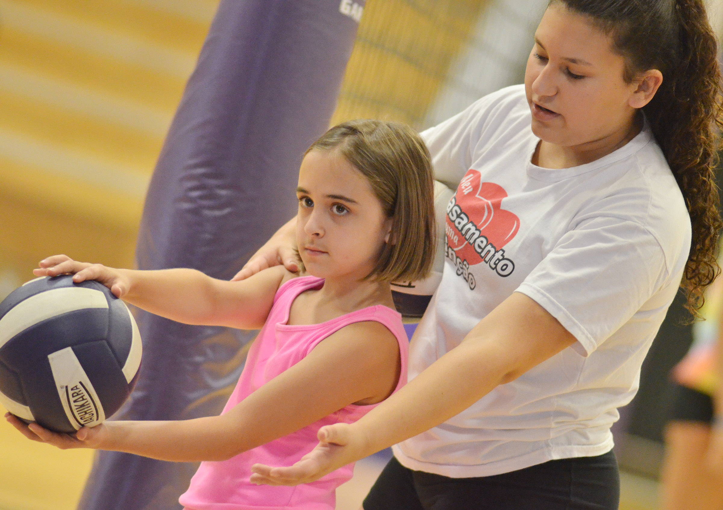 CHS freshman Anna Clara Moura helps CES fifth-grader Anna Floyd serve.