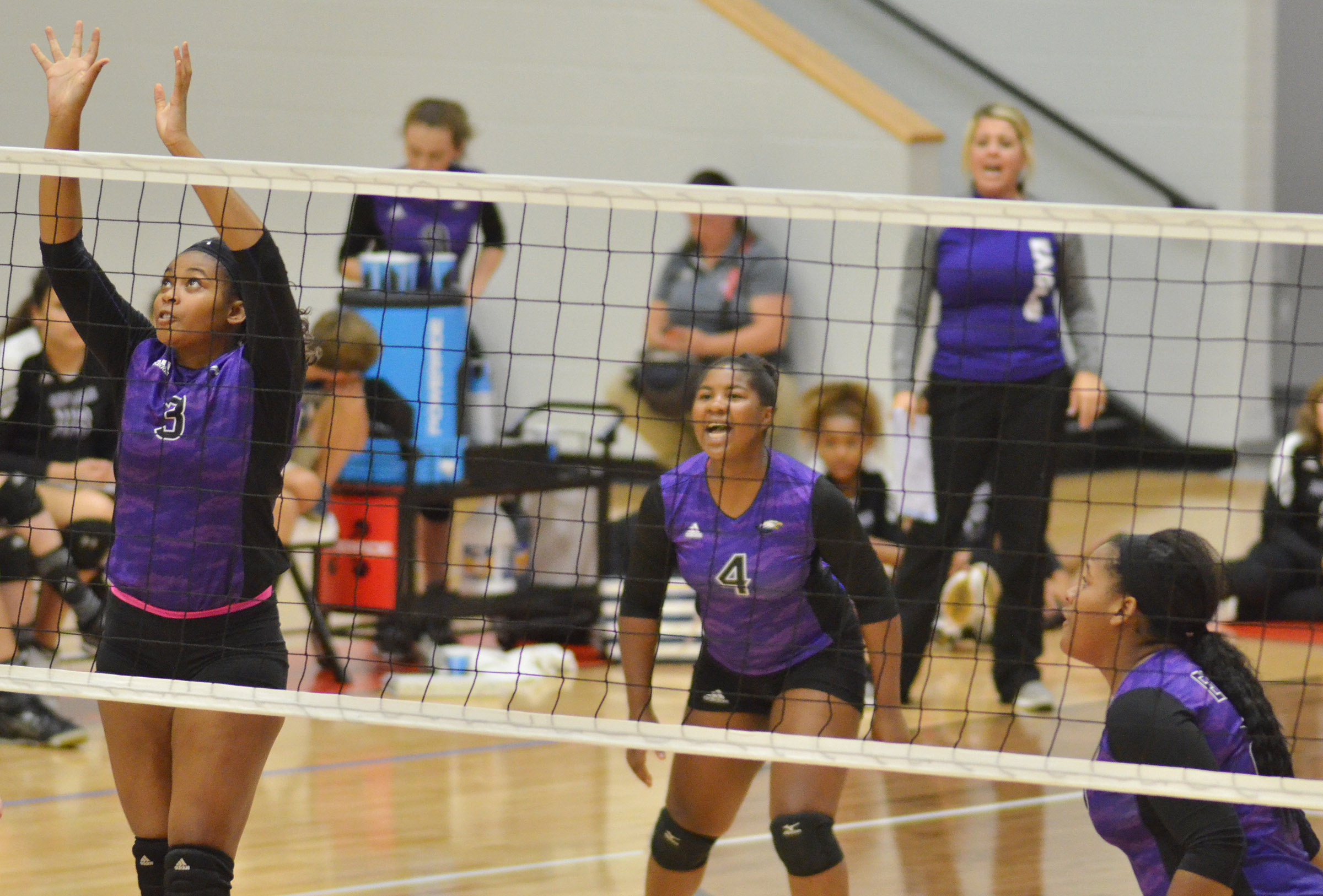 CHS senior Vonnea Smith jumps to block the ball, as classmates Nena Barnett and Kayla Young cheer for her.