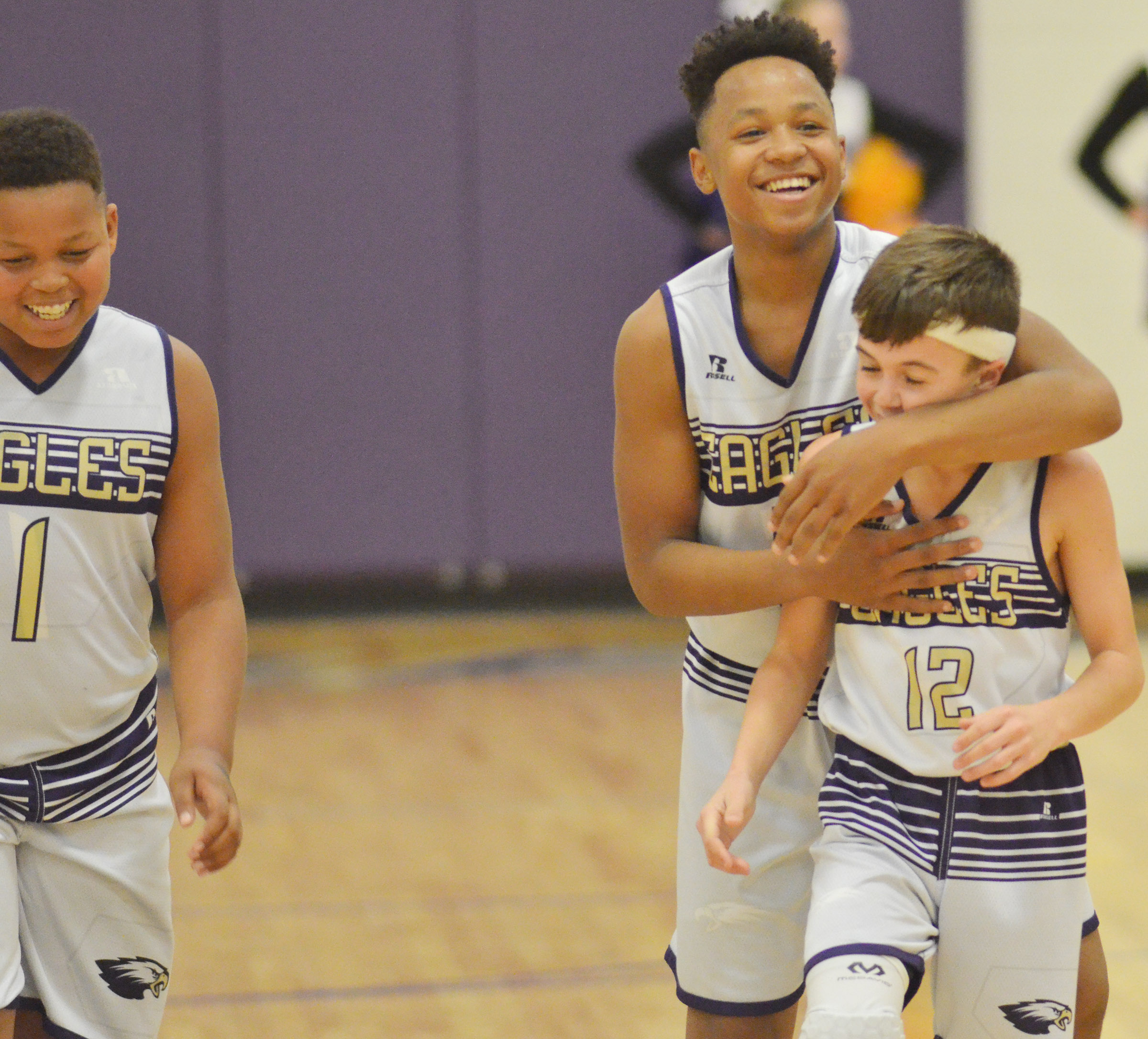 CMS seventh-graders, from left, Keondre Weathers, Deondre Weathers and Chase Hord celebrate after a play.