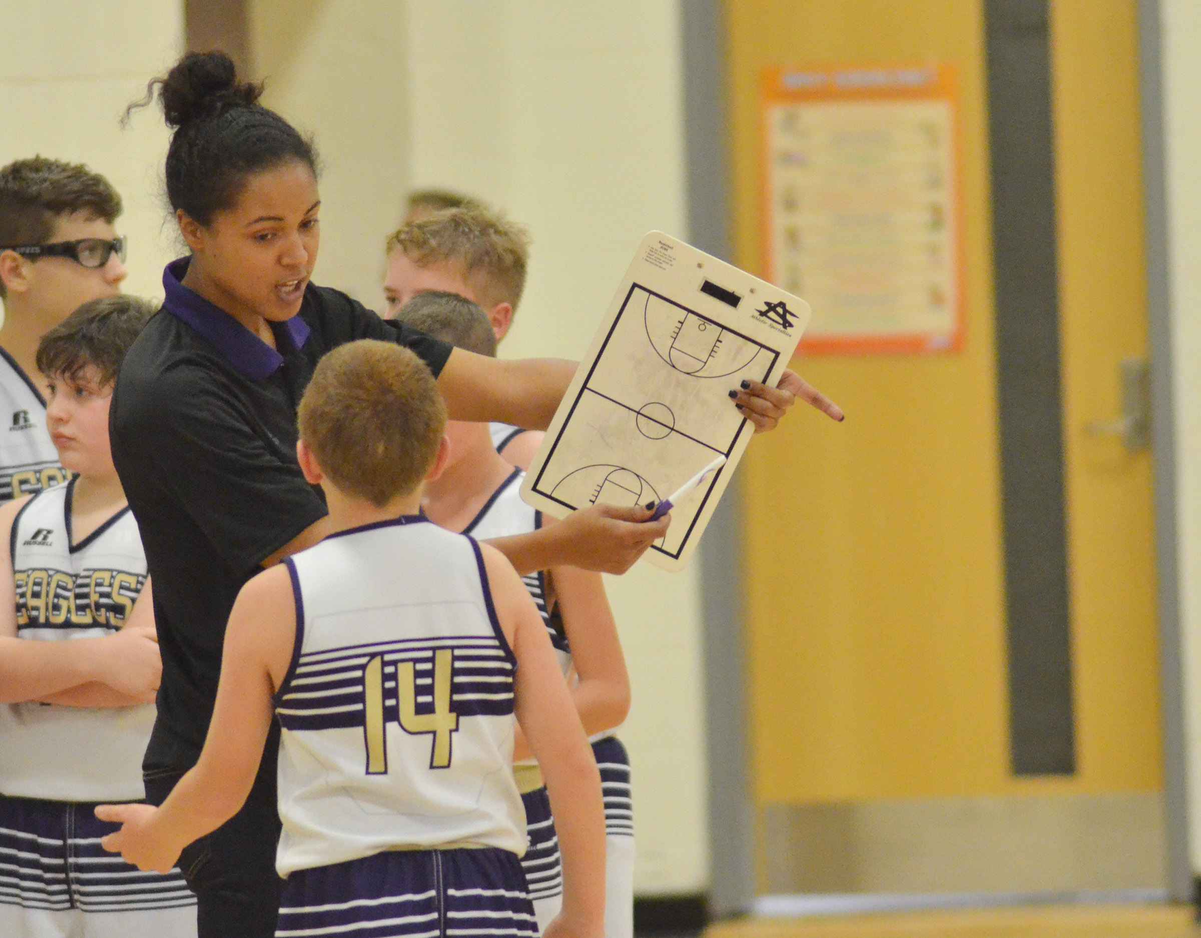CMS assistant boys' basketball coach Kyvin Goodin-Rogers talks to her players.