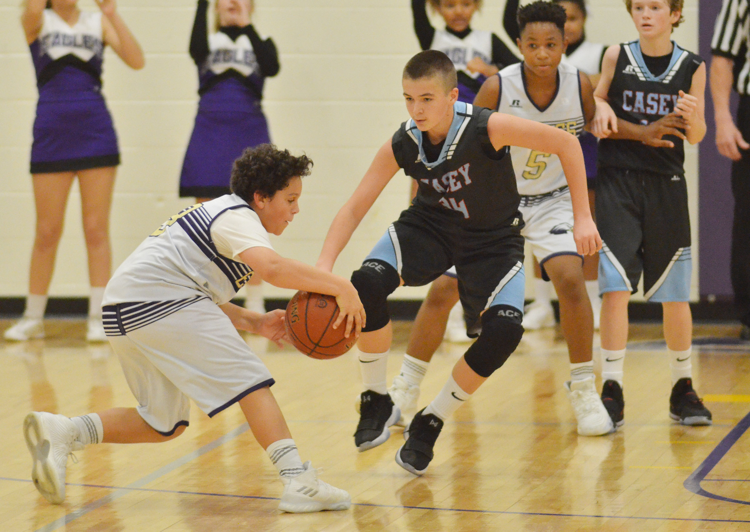 CMS seventh-grader Kaydon Taylor dribbles as classmate Deondre Weathers plays defense.