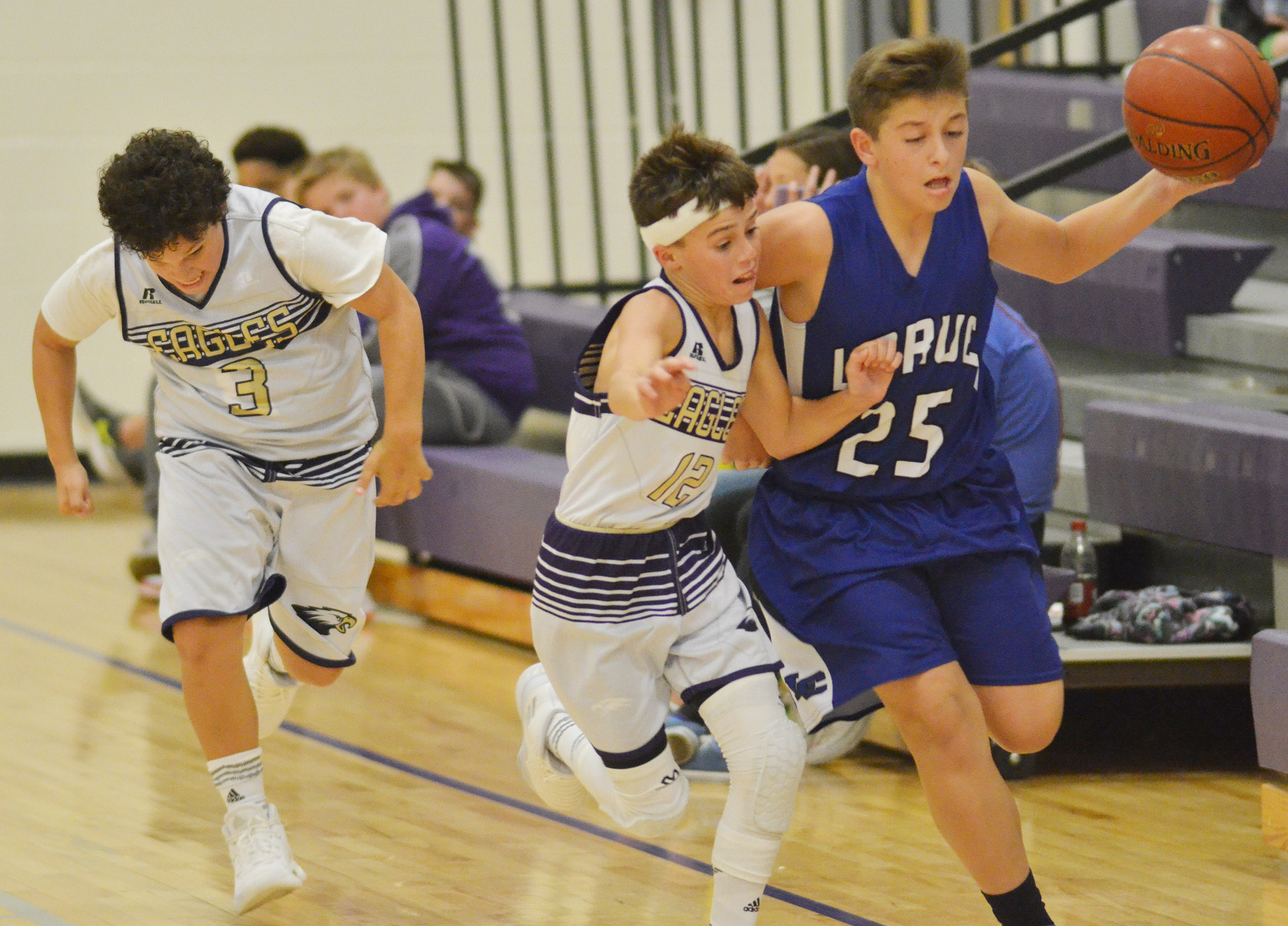 CMS seventh-grader Kaydon Taylor runs down the court as seventh-grader Chase Hord battles for the ball.