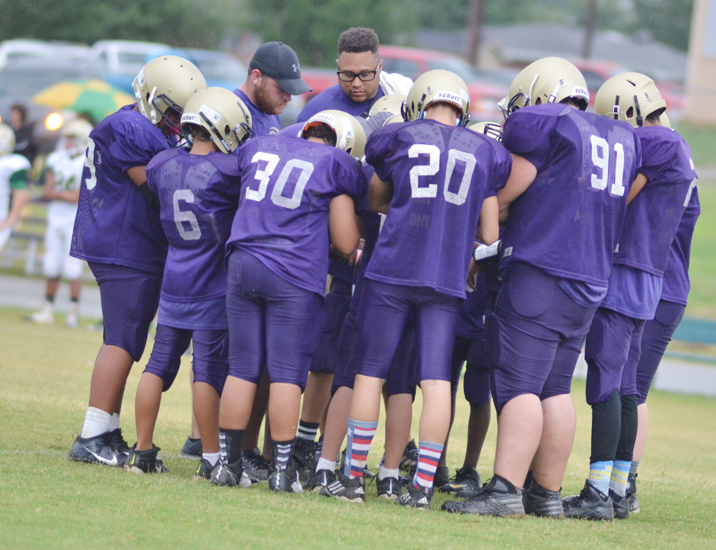 CMS football players huddle before a play.