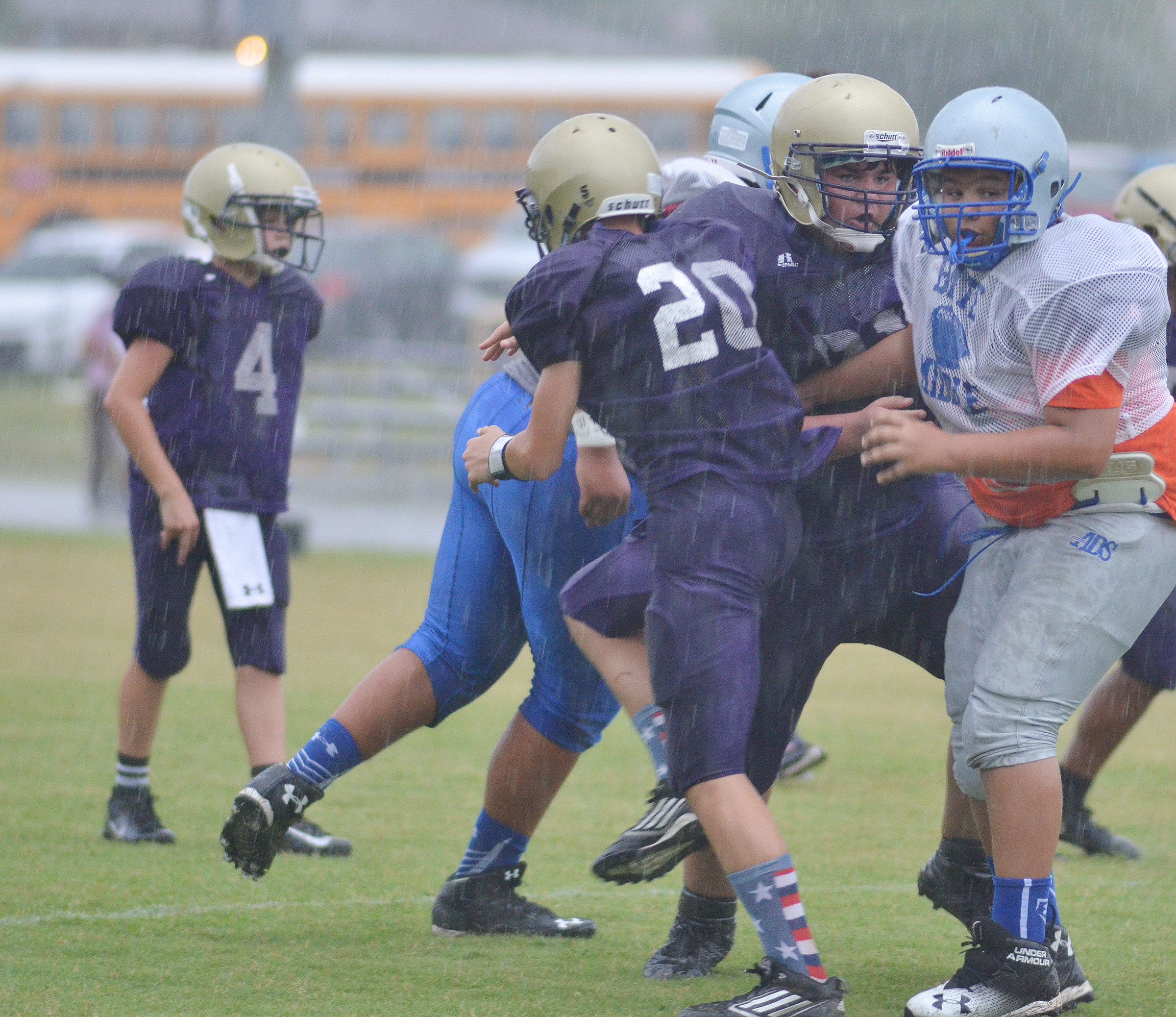 CMS seventh-grader Damon Johnson, center, and eighth-grader Logan Rakes tackle.