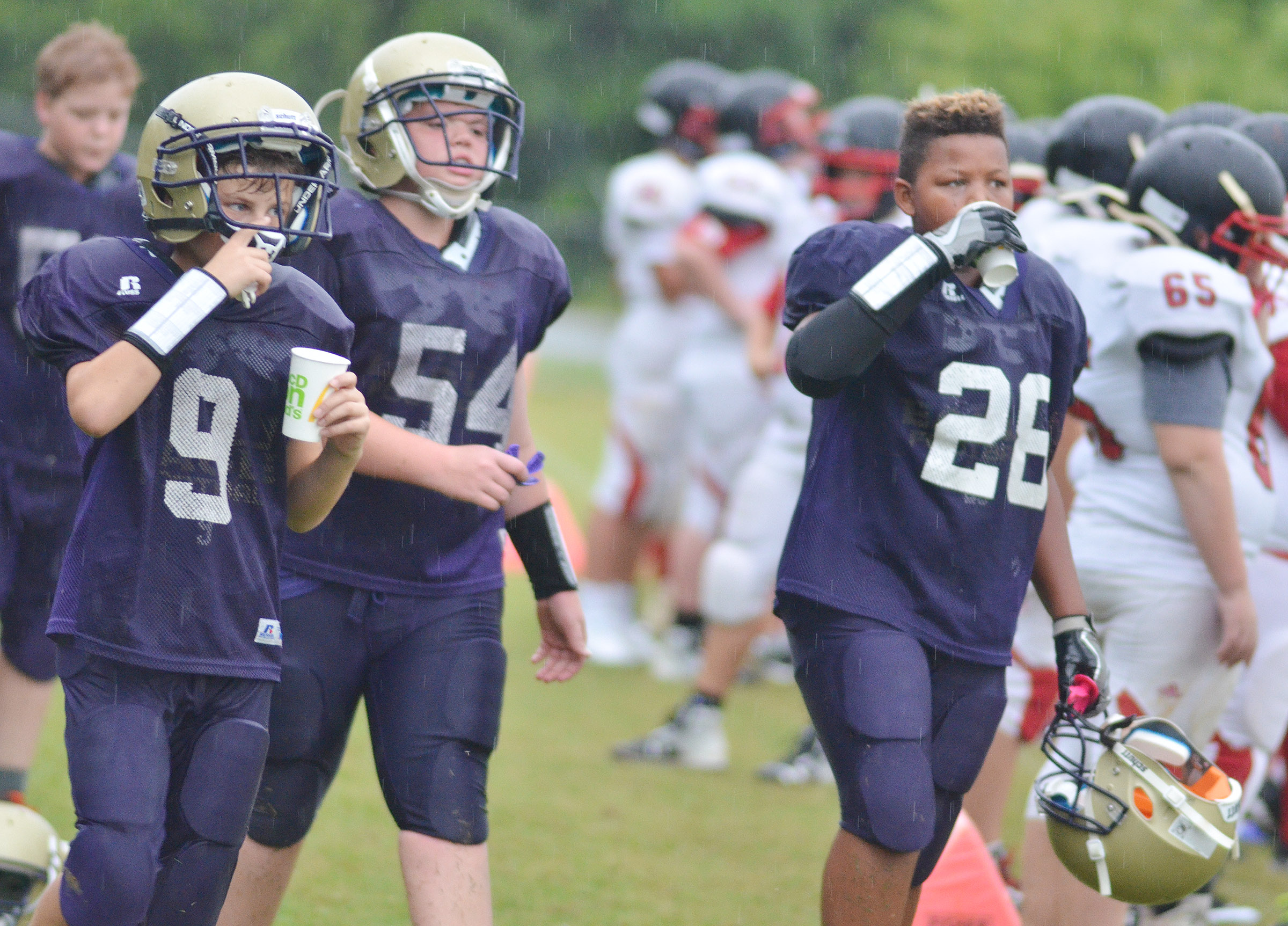 From left, sixth-grader Jaxon Sidebottom, and seventh-graders Hayden Jones and Keondre Weathers rest between plays.