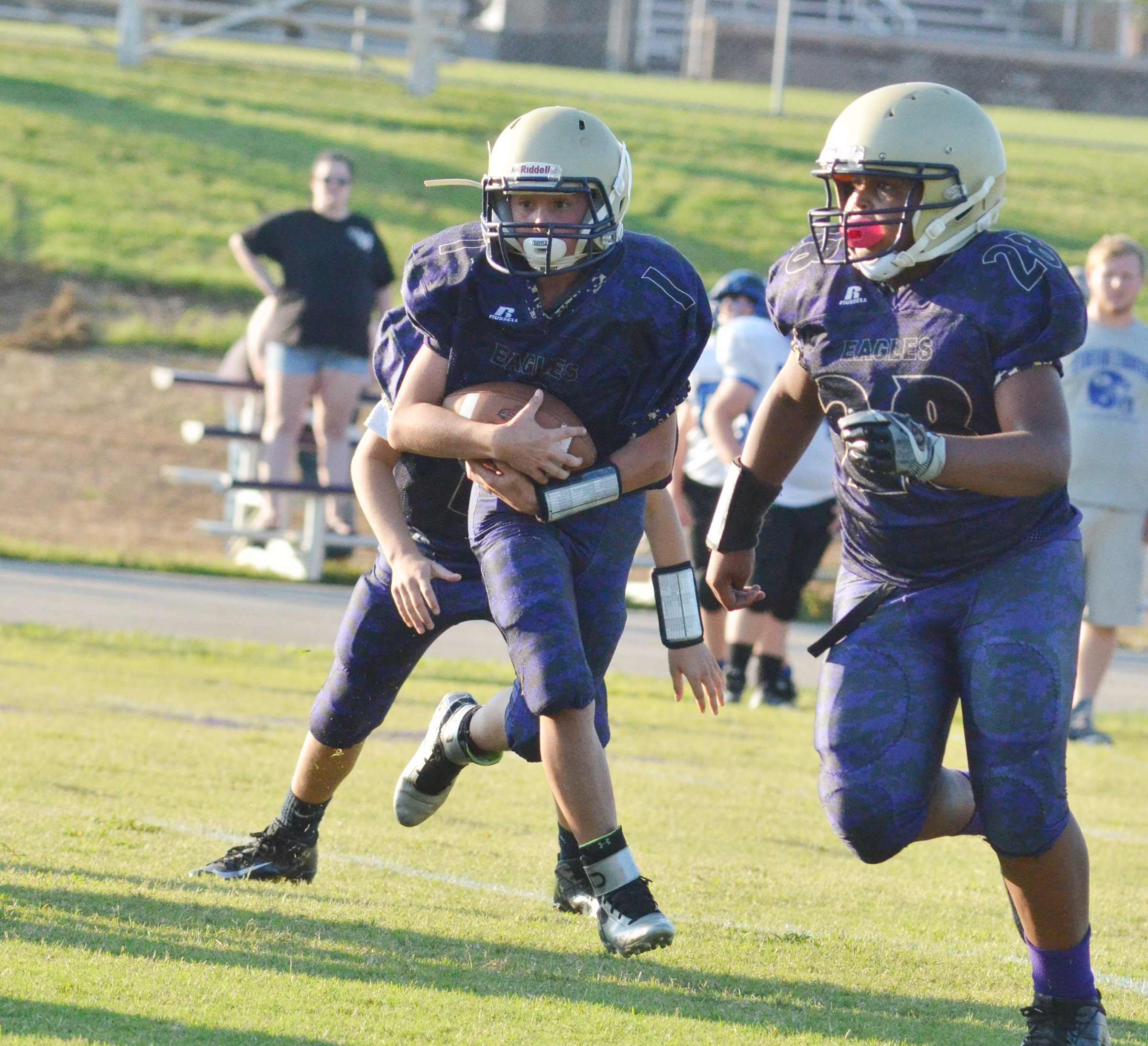 CMS eighth-grader Dakota Harris runs the ball as seventh-grader Keondre Weathers blocks.