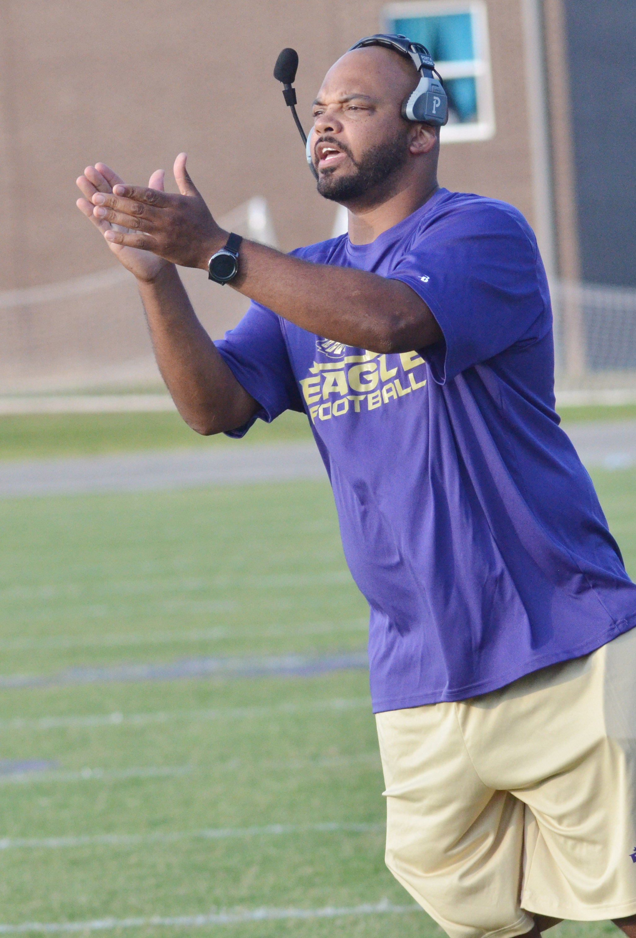 CMS head football coach Aaron Webb claps after a play.