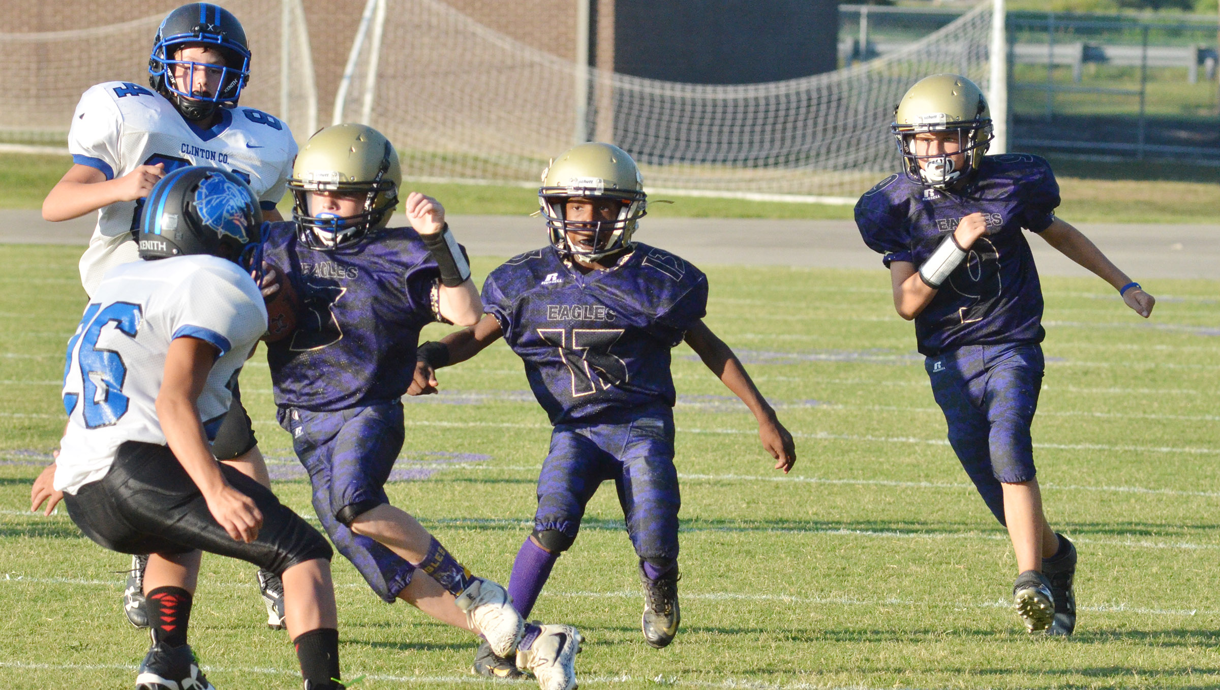 From left, CMS eighth-grader Tuff Harper runs the ball as classmate Jadan Furman and seventh-grader Jaxon Sidebottom block for him.