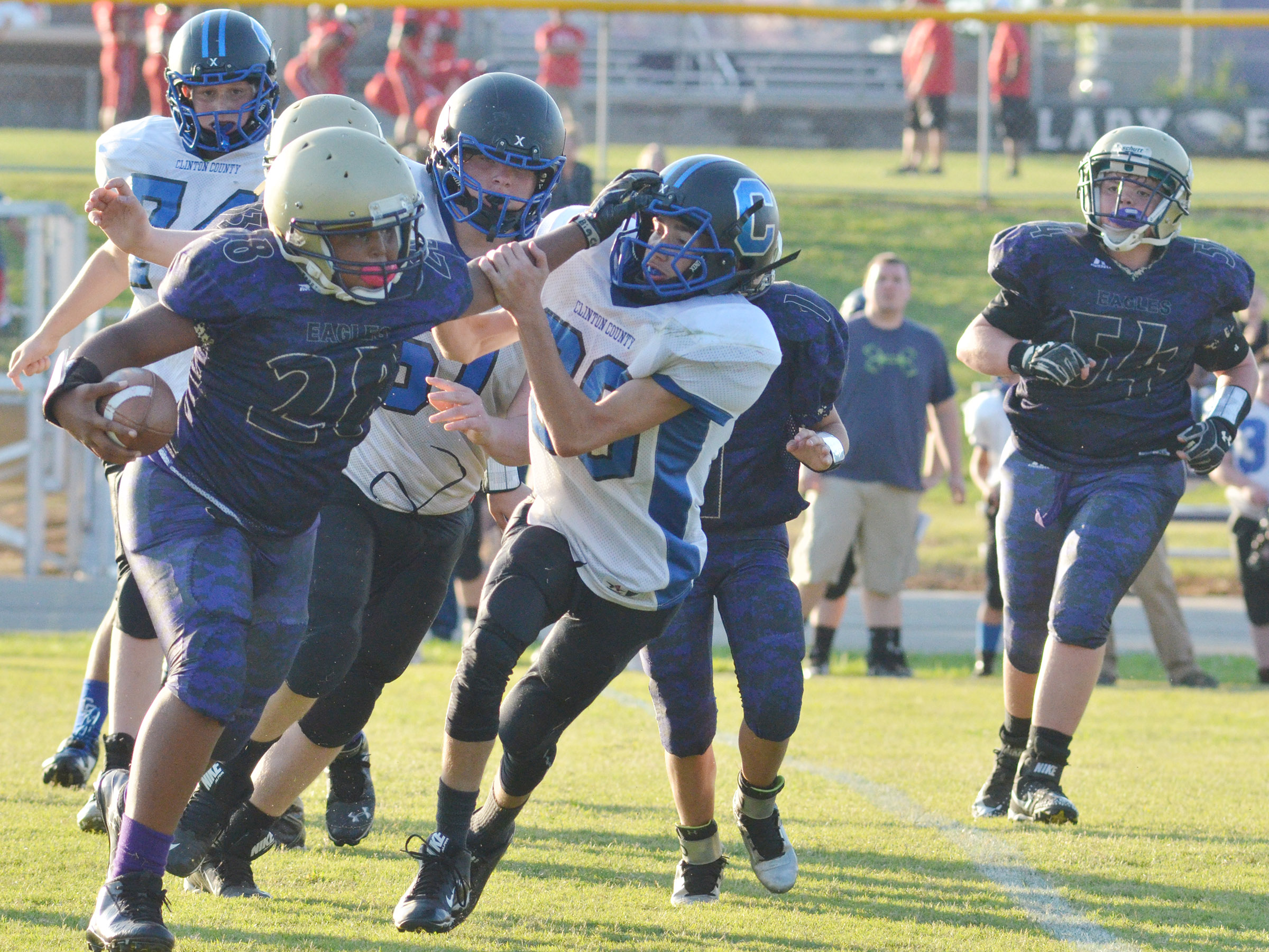 CMS seventh-graders Keondre Weathers blocks as he runs the ball.